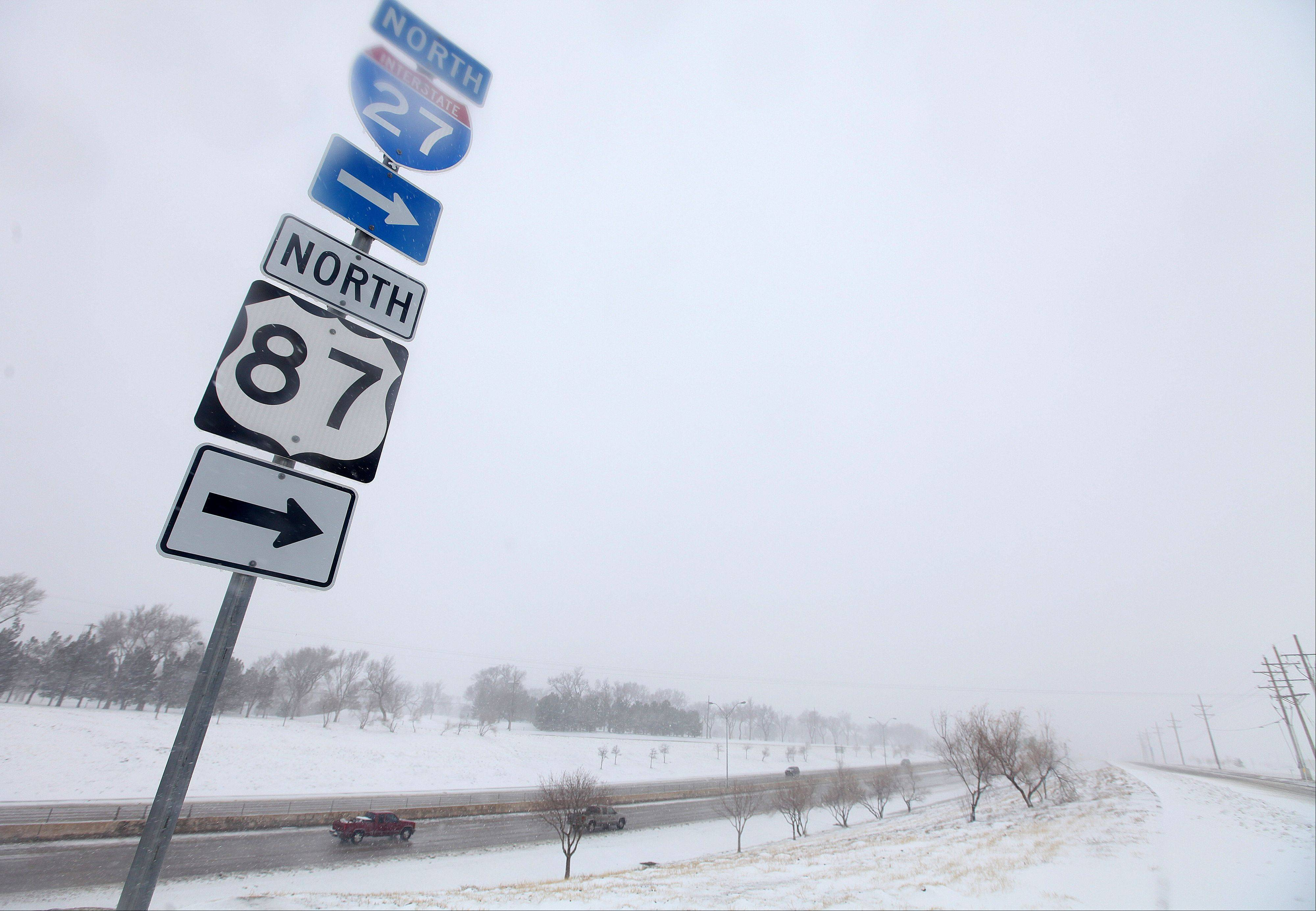 Vehicles navigate along Interstate 27 during blizzard conditions in Lubbock, Texas, Monday. State troopers are unable to respond to calls for assistance and National Guard units are mobilizing as a winter storm blankets the central Plains with a foot of snow in some places. Roads were closed Monday throughout West Texas and the Panhandle.