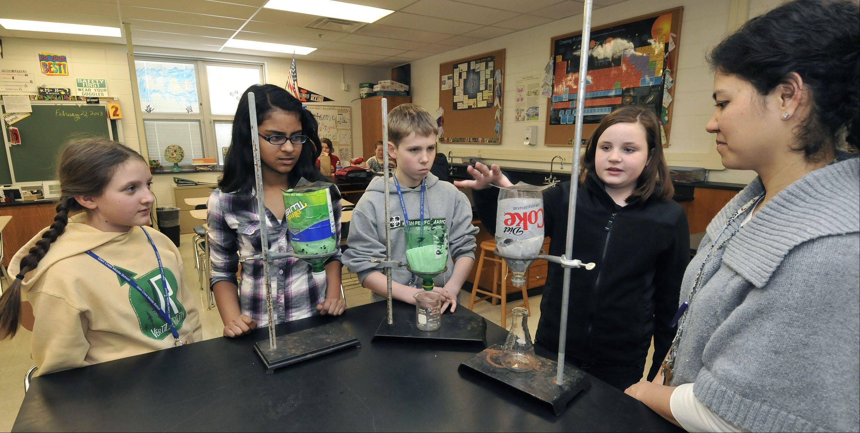 Glen Crest Middle School sixth-graders Molly Friedman, Sohini Surapaneni, Alex Bergendorf and Rachel Jordan join teacher Jennifer Rodriguez in demonstrating some of the experiments they did to purify water.