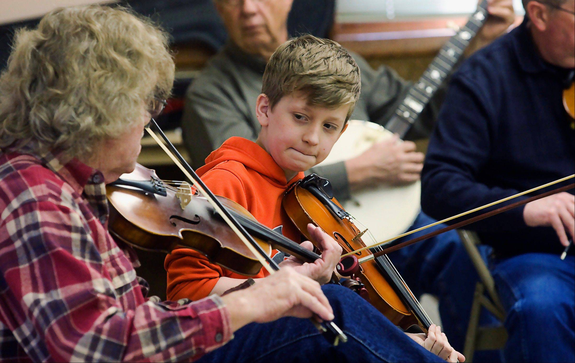 Dylan Haugh looks to his grandfather, Mike Haugh, as they play during the Illinois Old Time Fiddlers Association monthly jam in Shelbyville.