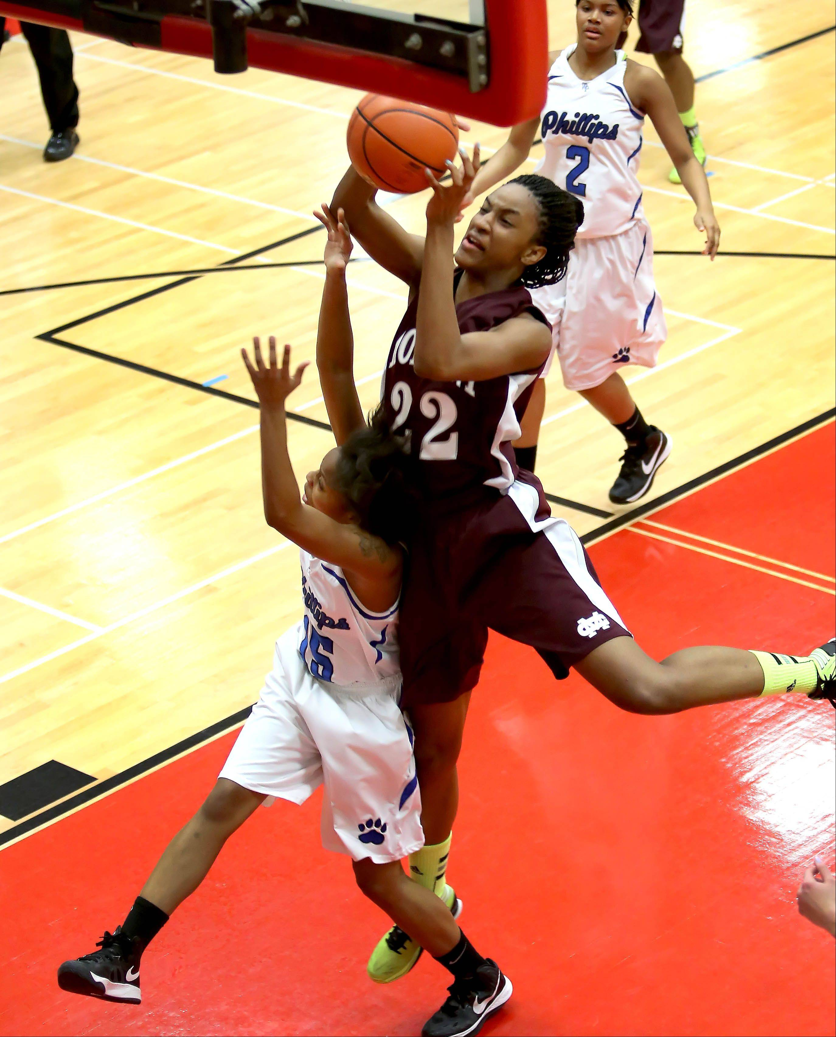 Malayna Johnson of Montini collides with Zemoria Jernigan of Phillips during Class 3A super sectional girls basketball on Monday at Hinsdale Central.