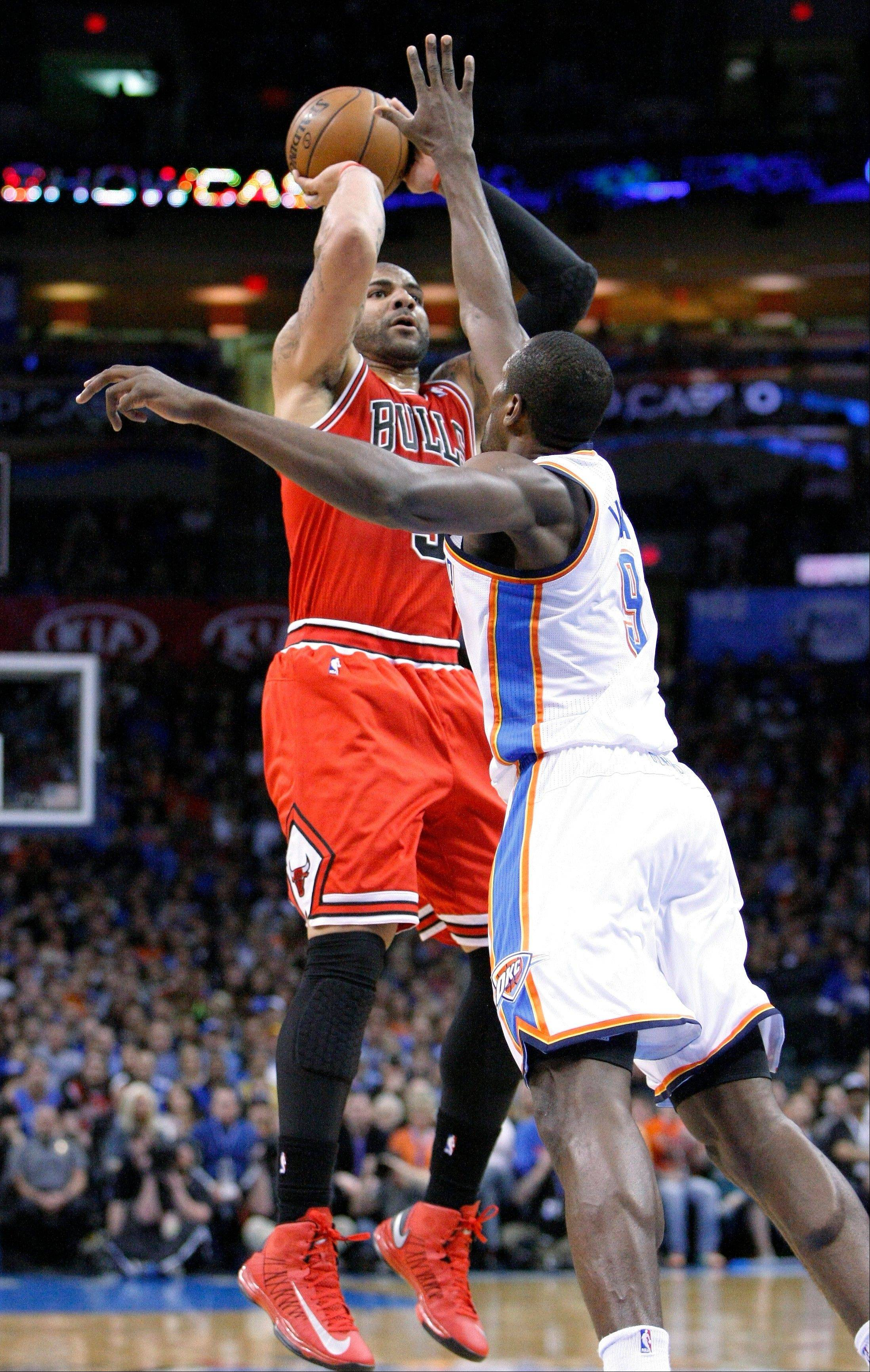 Bulls forward Carlos Boozer shoots over Thunder forward Serge Ibaka during Sunday night's 30-point loss at Oklahoma City.