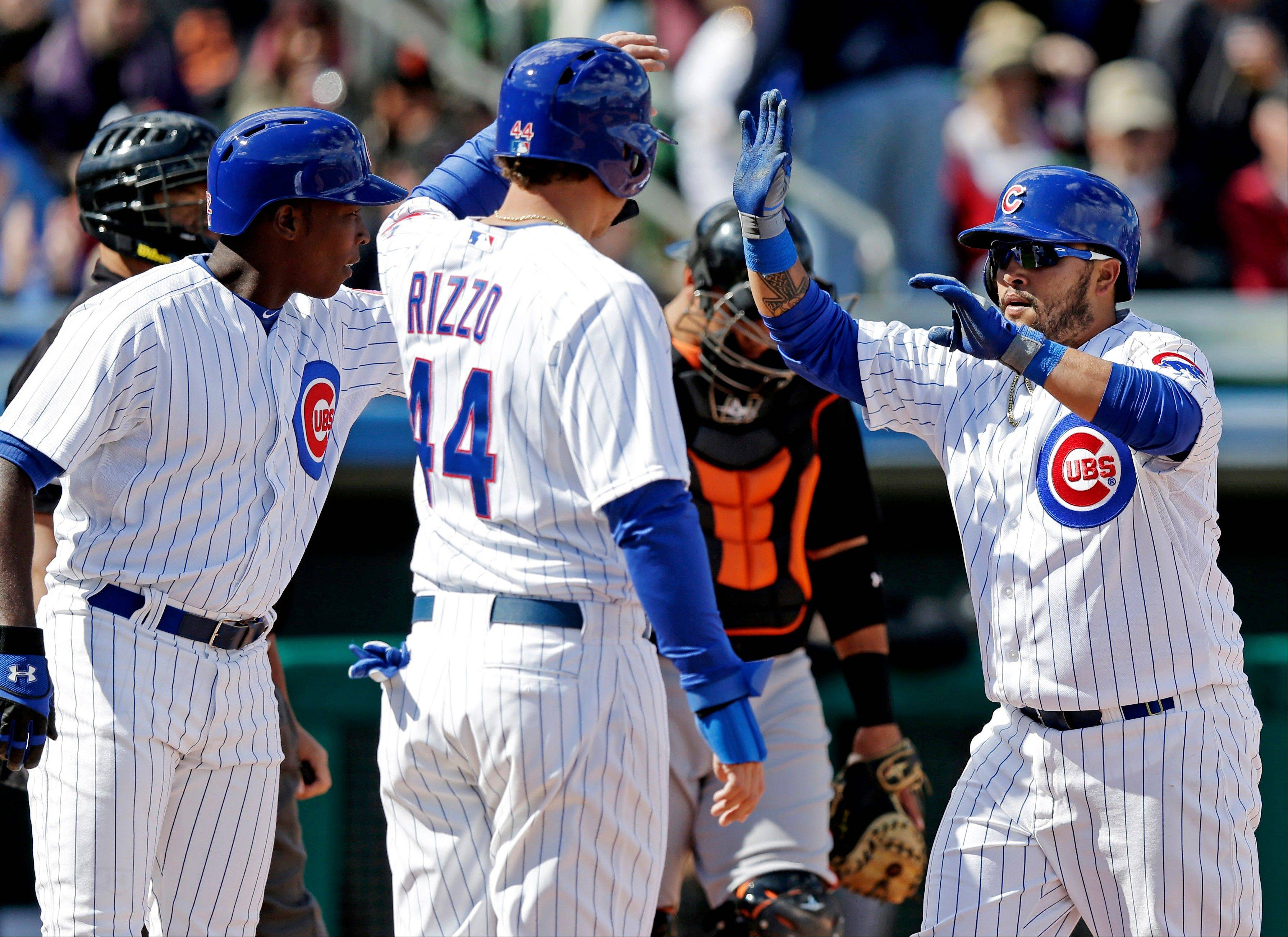 Chicago Cubs' Dioner Navarro, right, is congratulated by Anthony Rizzo (44) and Alfonso Soriano after hitting a three-run home run during an exhibition game against the San Francisco Giants on Sunday.