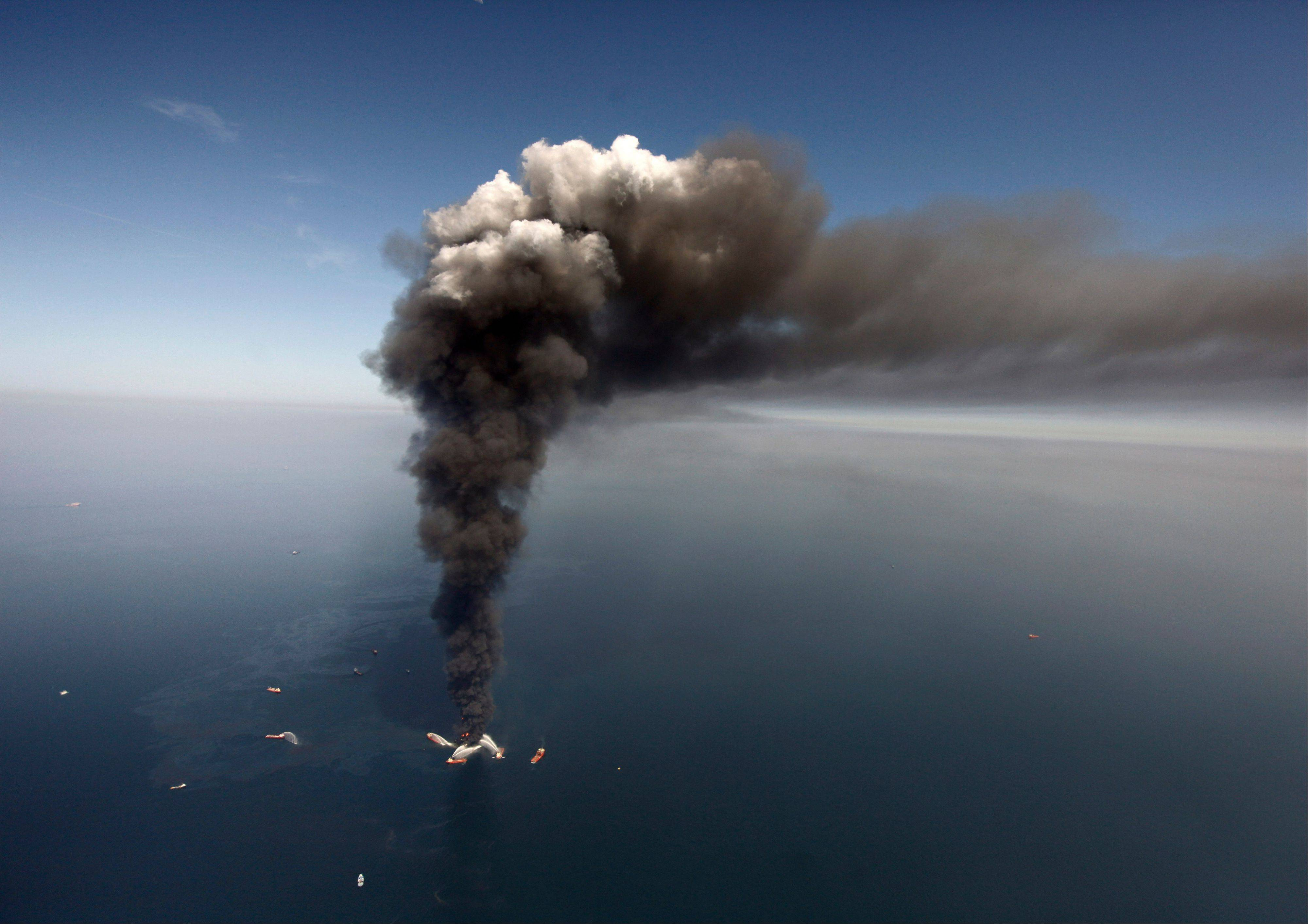 In this 2010 photo, oil can be seen in the Gulf of Mexico, more than 50 miles southeast of Venice on Louisiana's tip, as a large plume of smoke rises from fires on BP's Deepwater Horizon offshore oil rig.