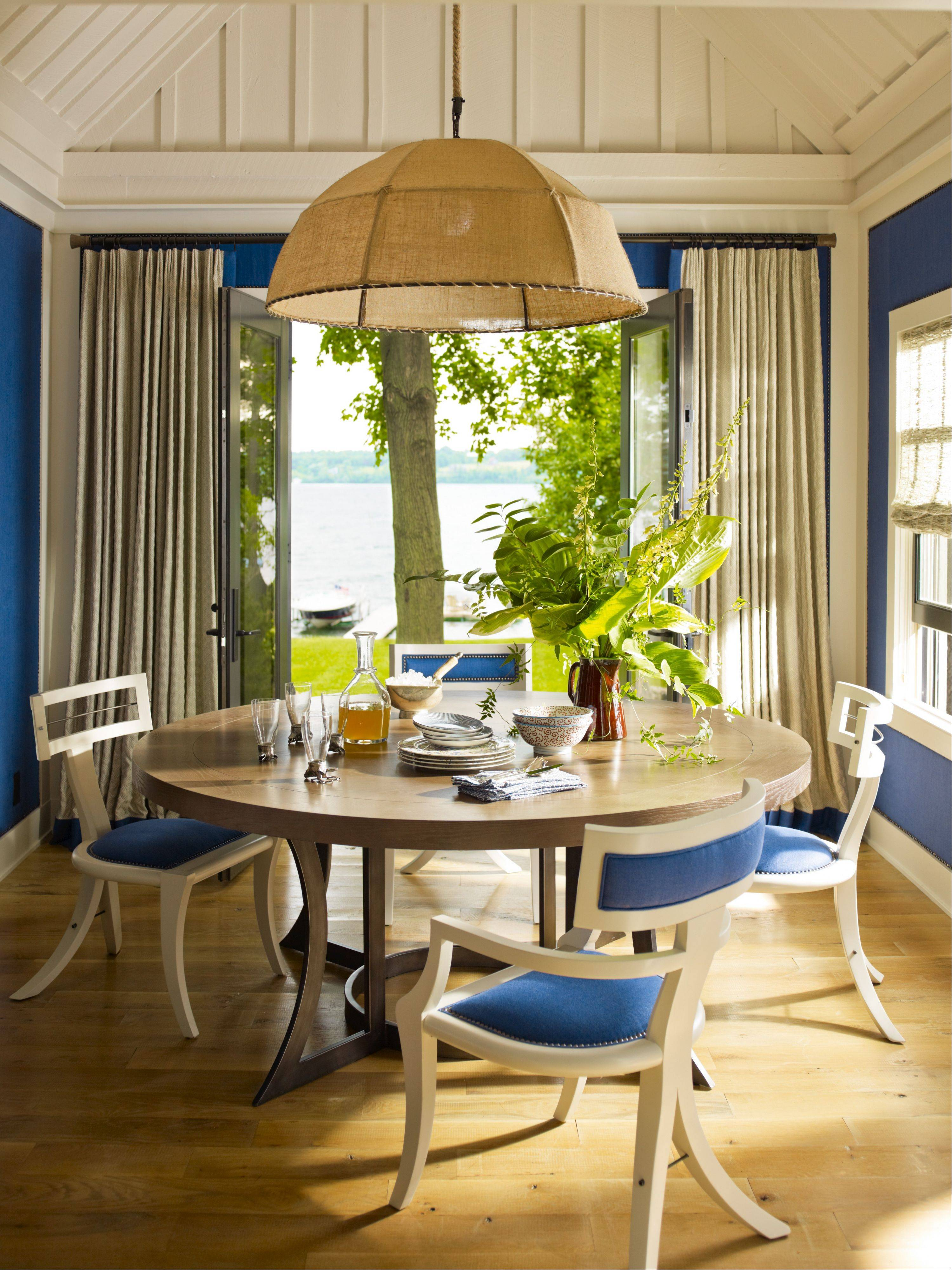 Reflective nail heads and white trim create a tailored look that means the dining room can carry a deep blue on walls and chairs.