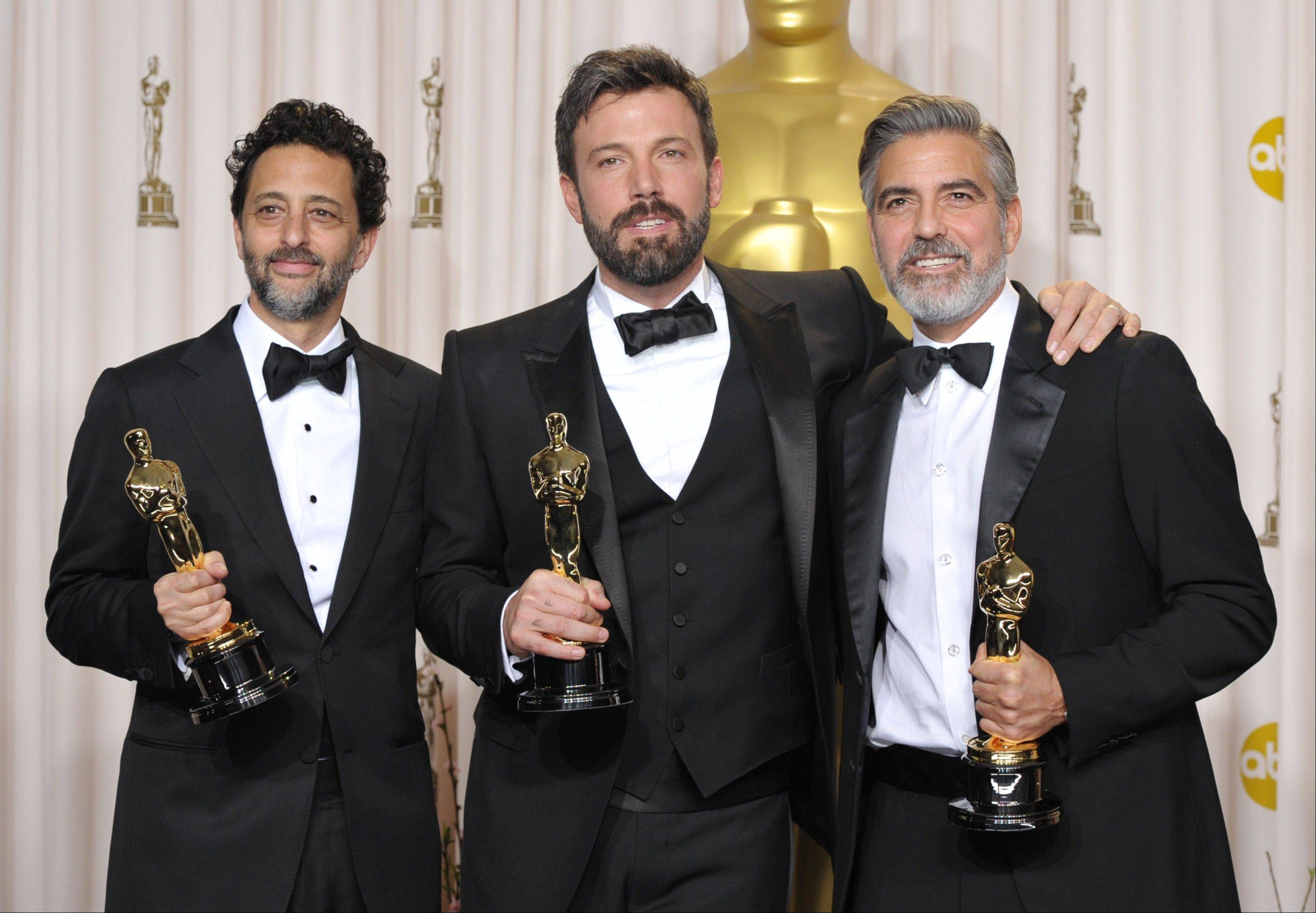"Grant Heslov, left, Ben Affleck and George Clooney pose with their award for best picture for ""Argo"" during the Oscars on Sunday in Los Angeles."