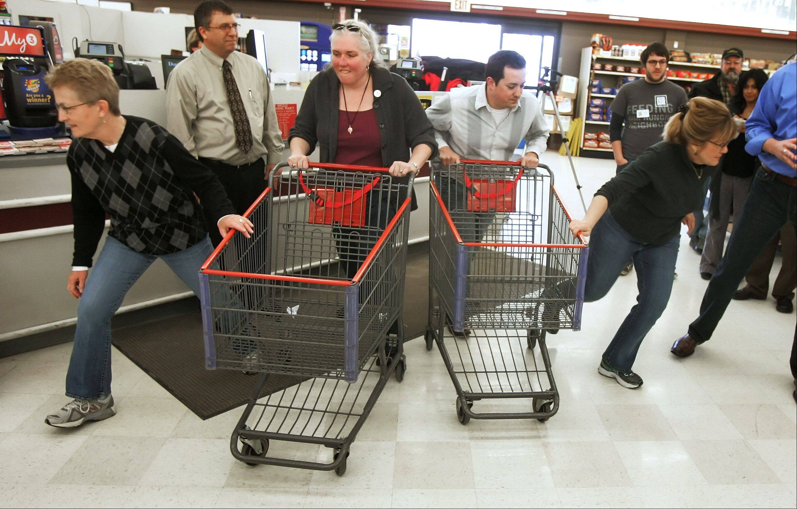 Lake County Board member Pat Carey, left, and state Sen. Melinda Bush, right, begin a 5-minute sprint through the grocery aisles Monday at the Piggly Wiggly store in Antioch for the 15th Annual Race for Hunger. The annual event sponsored by the Lake County Farm Bureau benefits local food pantries.