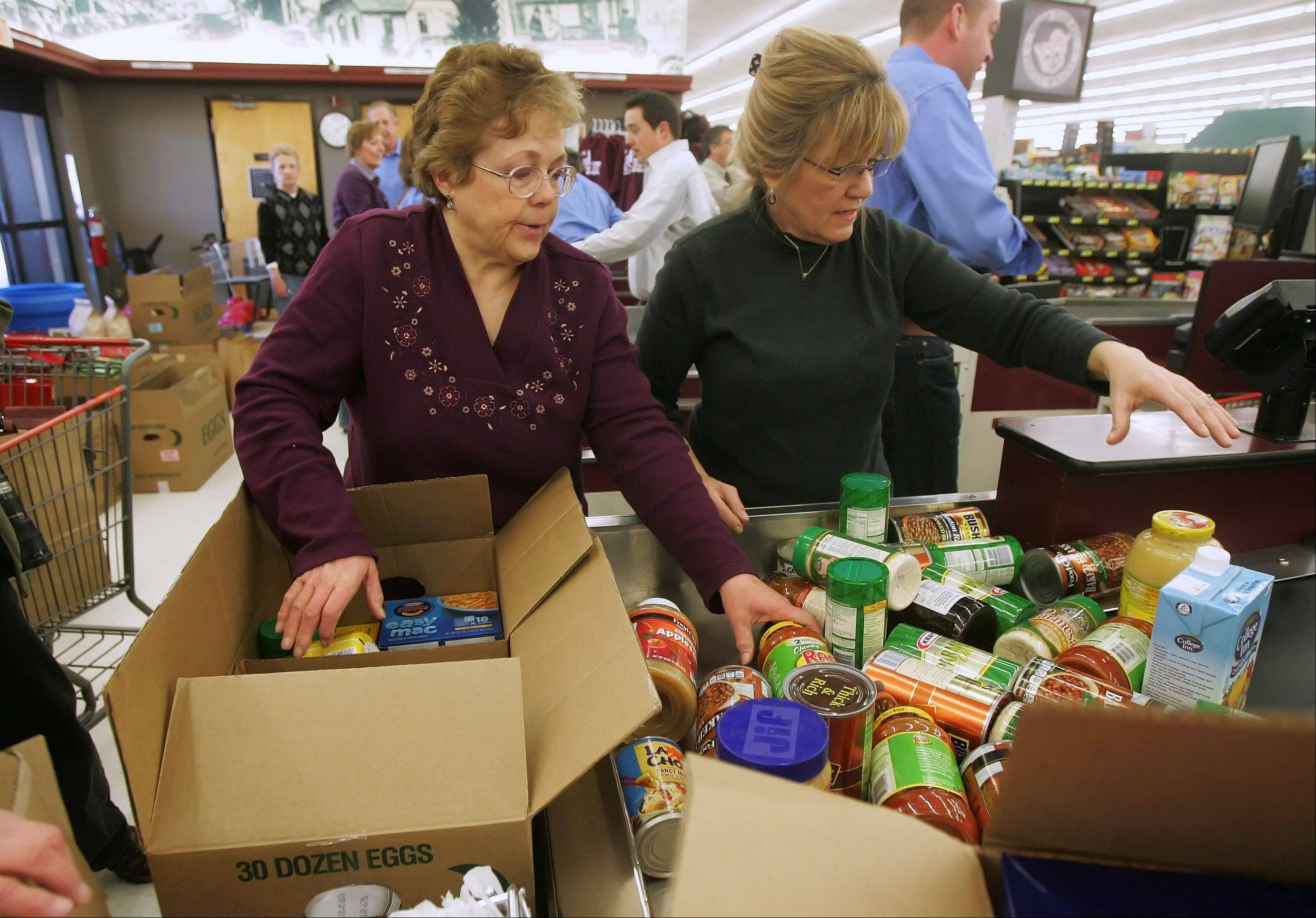 Volunteer Lynn Doolittle, left, helps state Sen. Melinda Bush box food she collected during the 15th Annual Race for Hunger Monday at the Piggly Wiggly grocery store in Antioch. The race was sponsored by the Lake County Farm Bureau to raise awareness of Food Check Out Week and provide goods for local food pantries.
