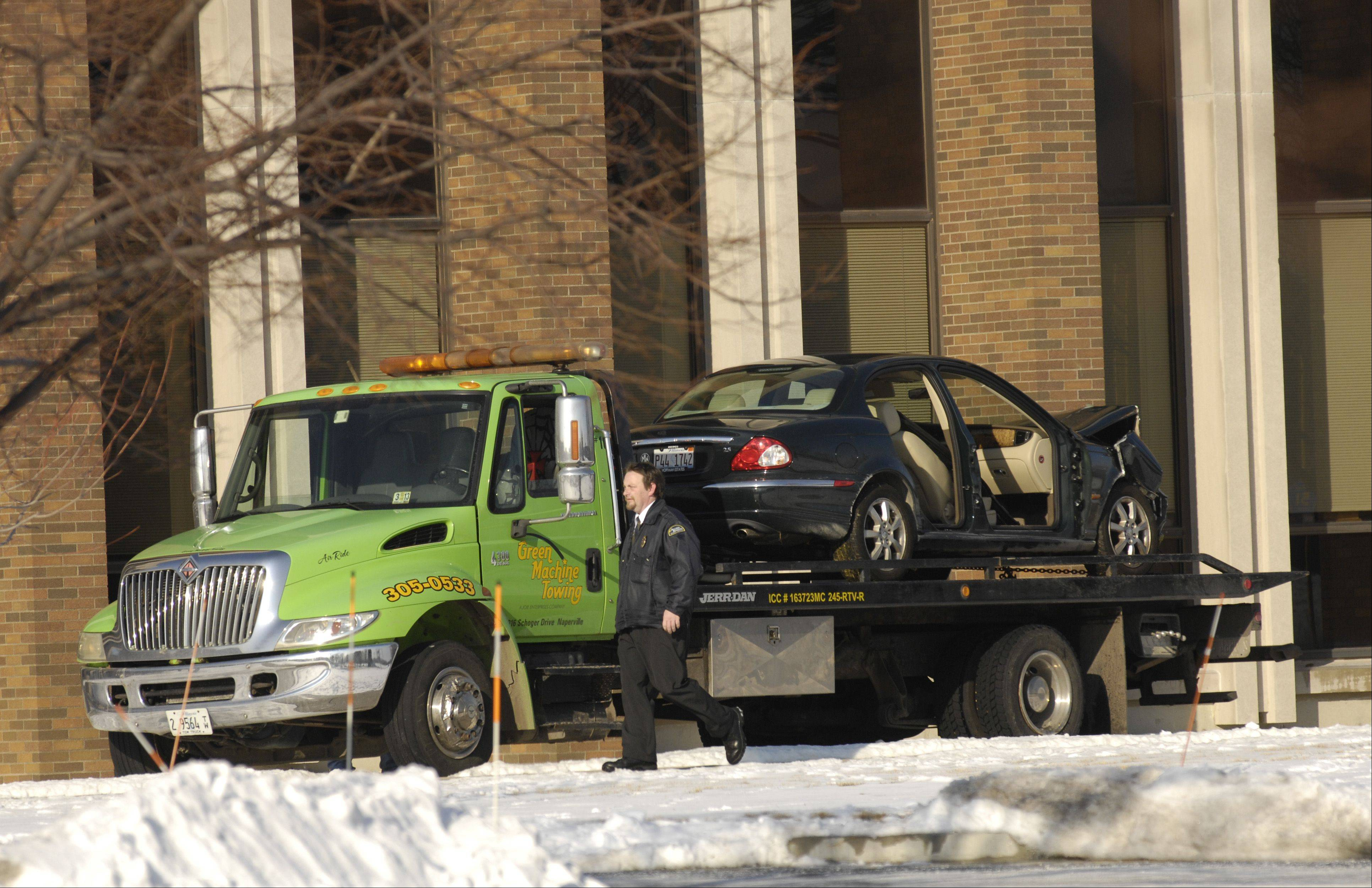 A car is removed from the scene after striking a building that houses DePaul University's Naperville campus. No one was seriously injured.