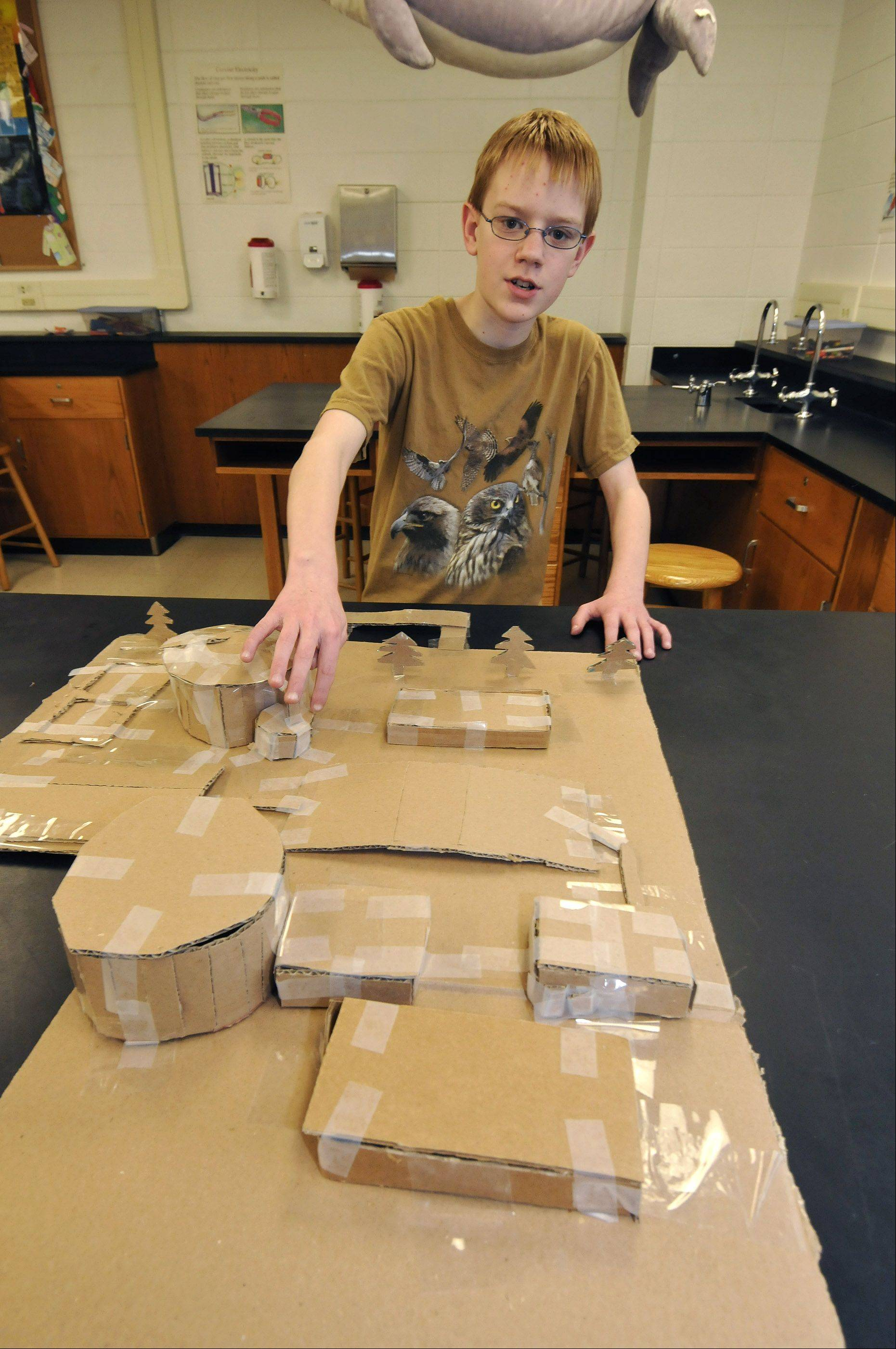 Sixth-grader Wesley Jedlicka explains the operation of a water purification plant with the aid of a cardboard model he built.