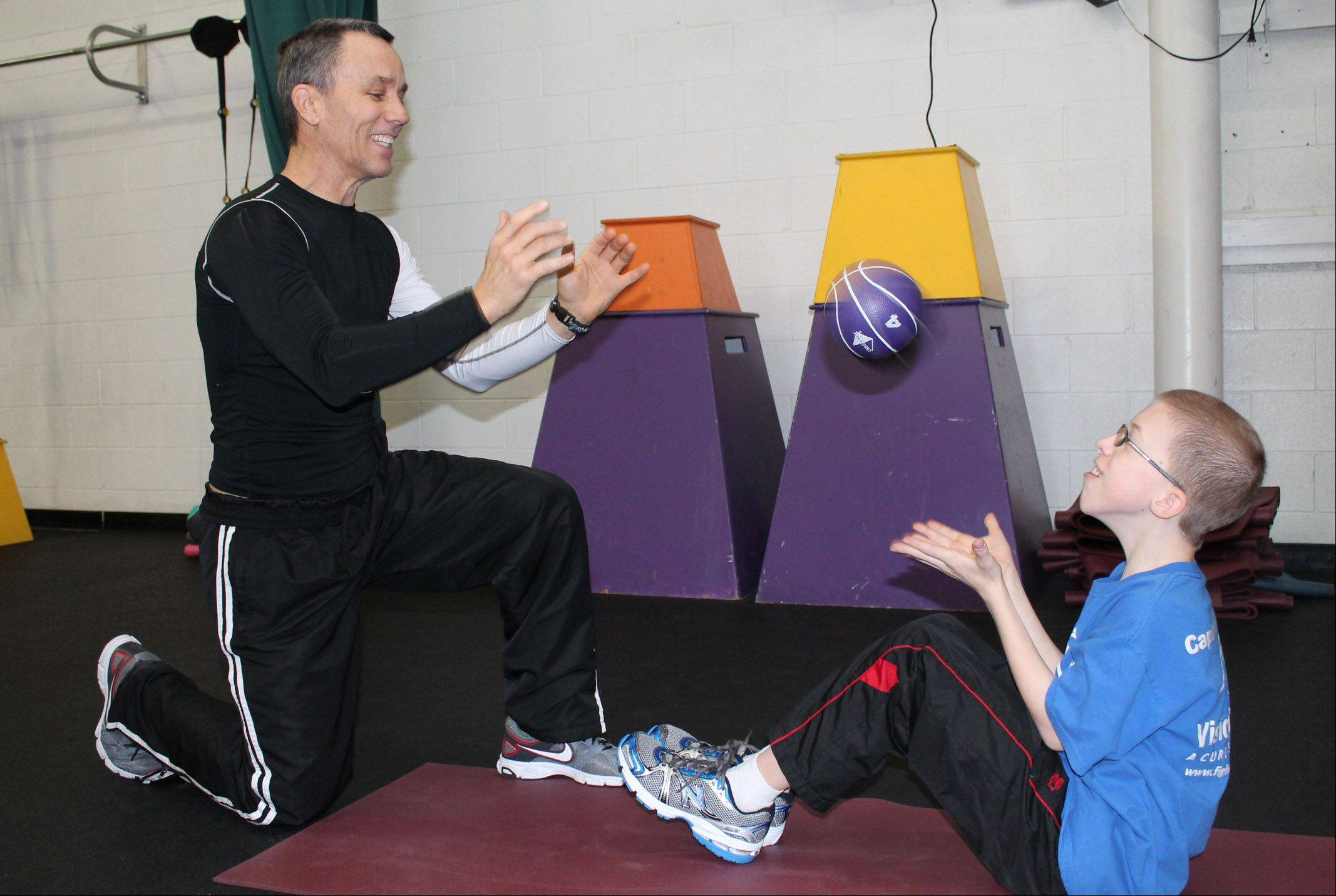 Jim O'Hara, left, works out with Nathan Hayes at Focus Martial Arts and Fitness in Lake in the Hills. Nathan has been named the co-youth chair of the eighth annual Foundation Fighting Blindness VisionWalk, which will take place June 9 in Elk Grove Village.