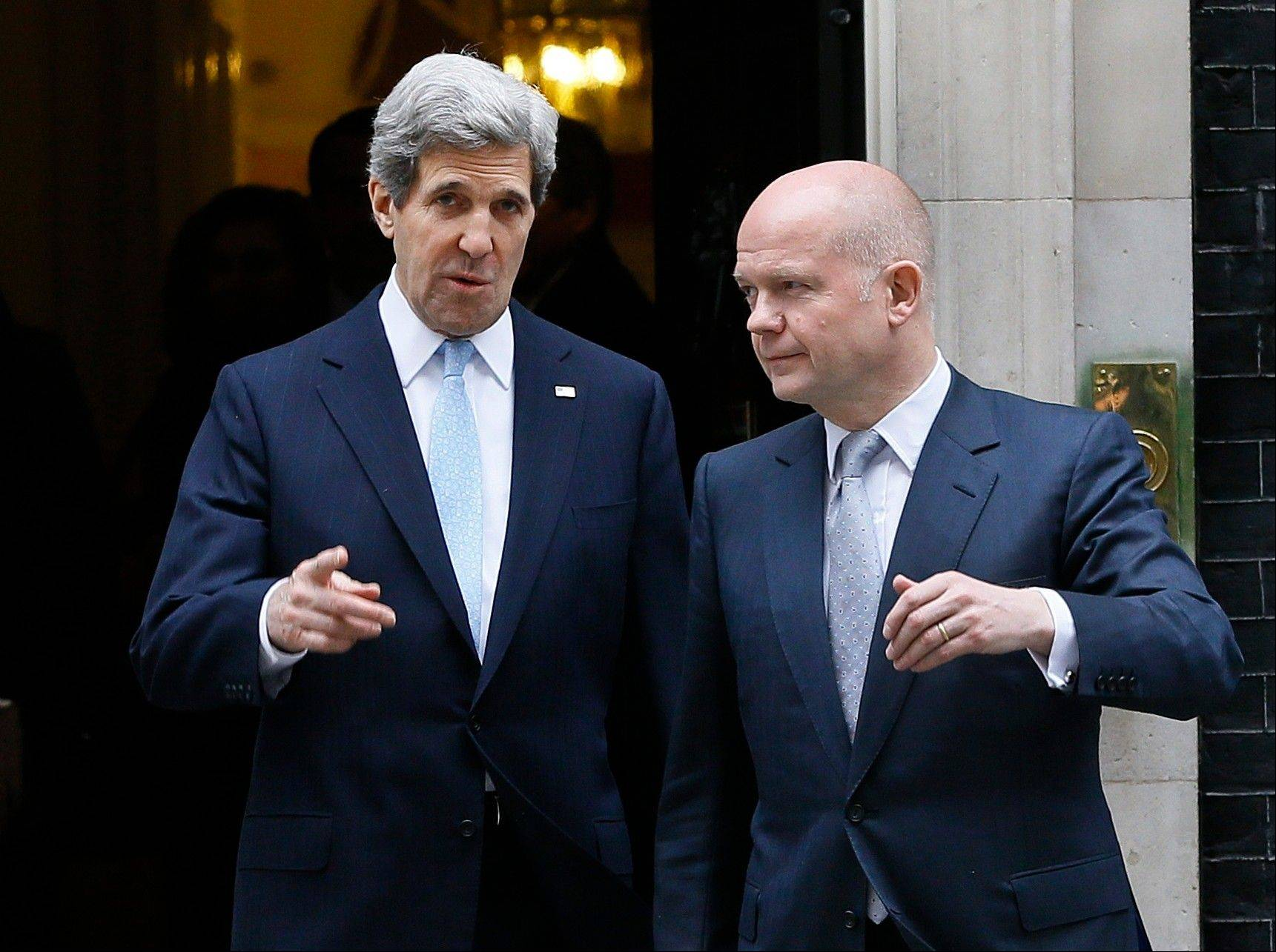 U.S. Secretary of State John Kerry, left, walks with British Foreign Secretary William Hague as they leave Downing Street in London, Monday. Kerry has kicked off his first official overseas trip by meeting with British leaders in London on the first leg of a hectic nine-day dash through Europe and the Middle East.