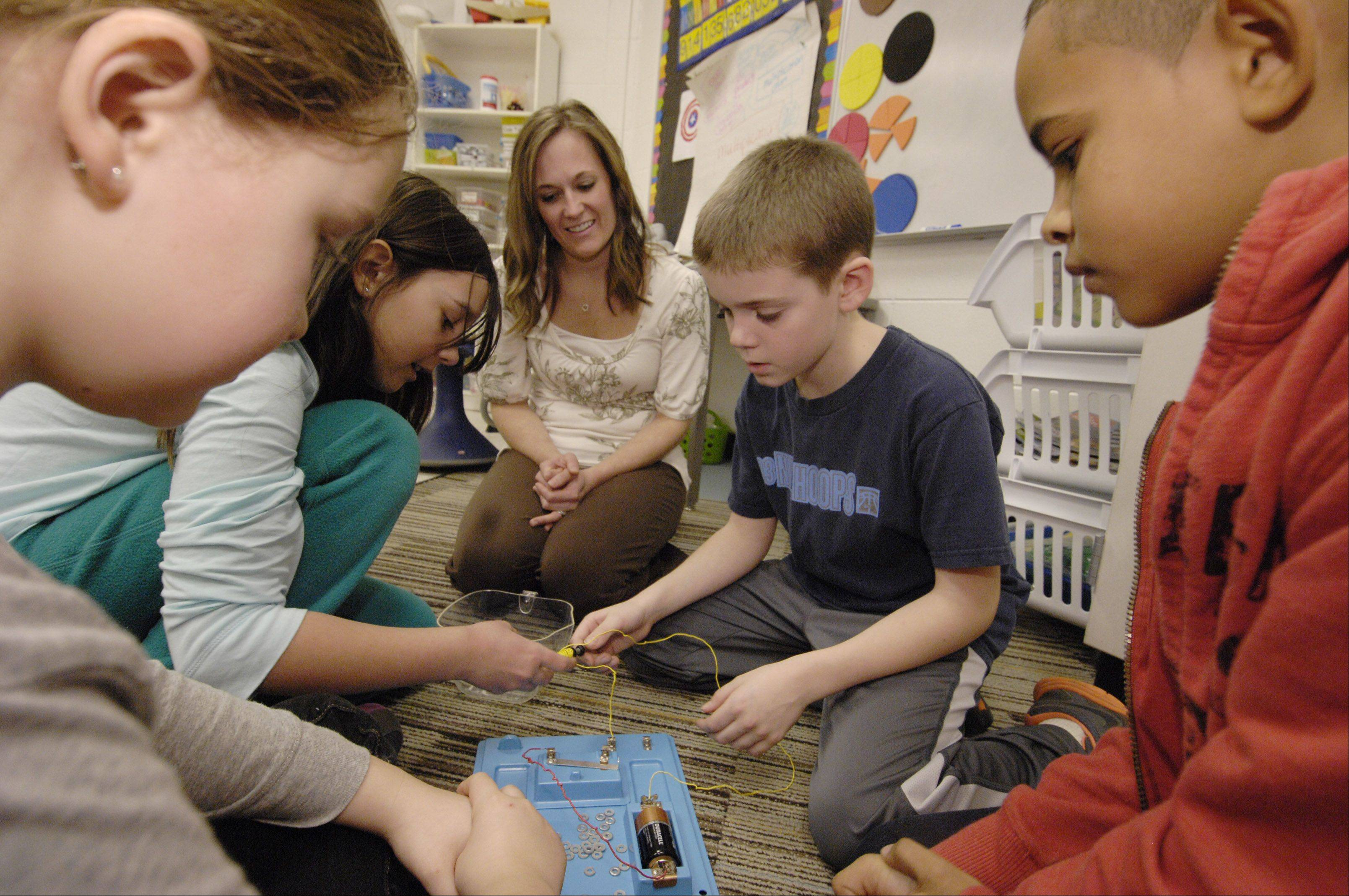 Fourth-grade students Alice Gramlich, Lilia Carman, Zach Bertrand and Ajani Rowland work on an electromagnet project with teacher Dee Dee Aldrich at Churchill Elementary School in Glen Ellyn. District 41 officials are proposing to combine grade levels as part of an effort to better focus on science, math and literacy instruction.