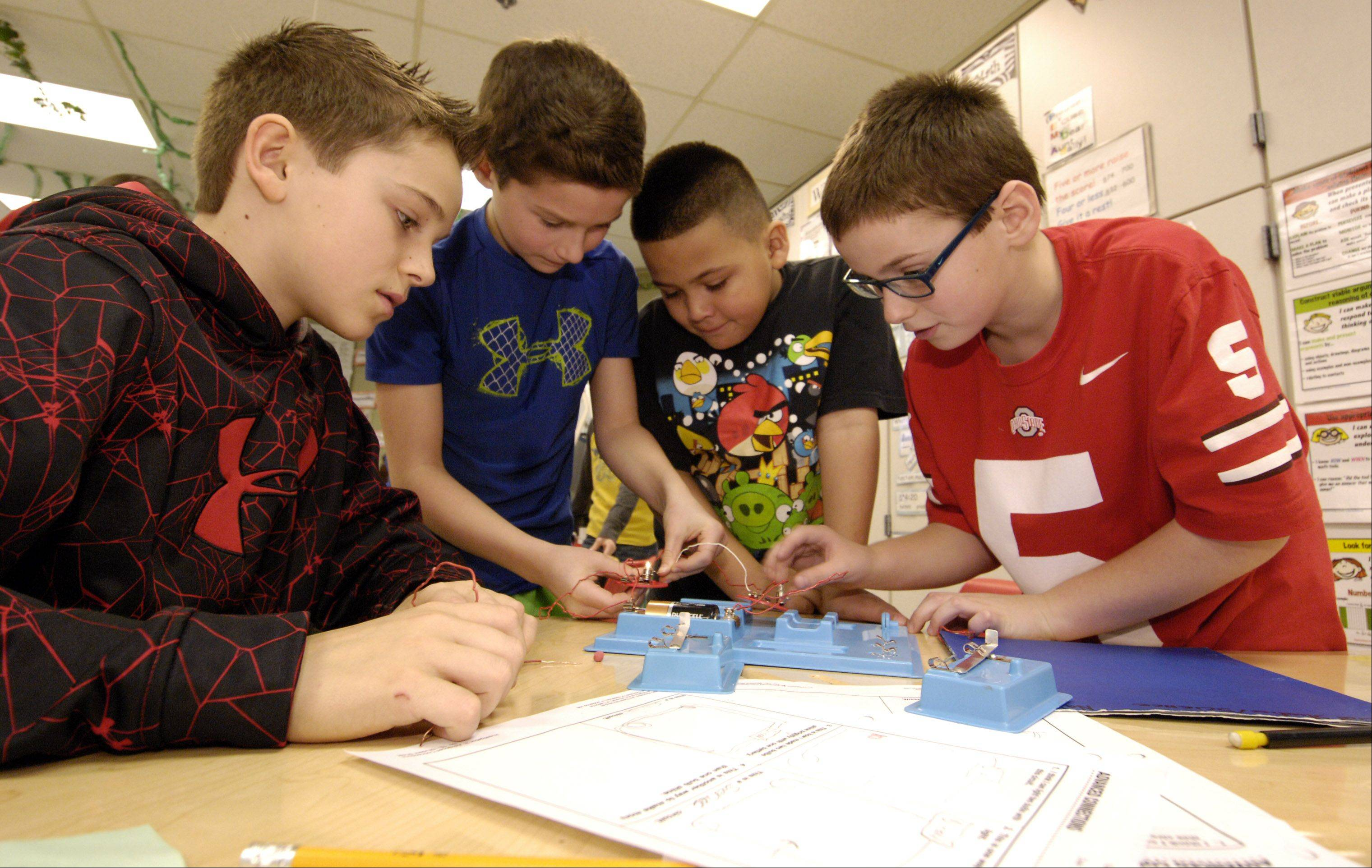 Mark Black/mblack@dailyherald.com ¬ Fourth grade students, Michael Rossi Nathan Navarro, Mario Vences and Luke Sullivan work on their an electricity science project at Churchill School. Glen Ellyn School District 41 is proposing to combine classes as part of the Think Tank initiative, in an effort to better focus on science, math and literacy instruction.
