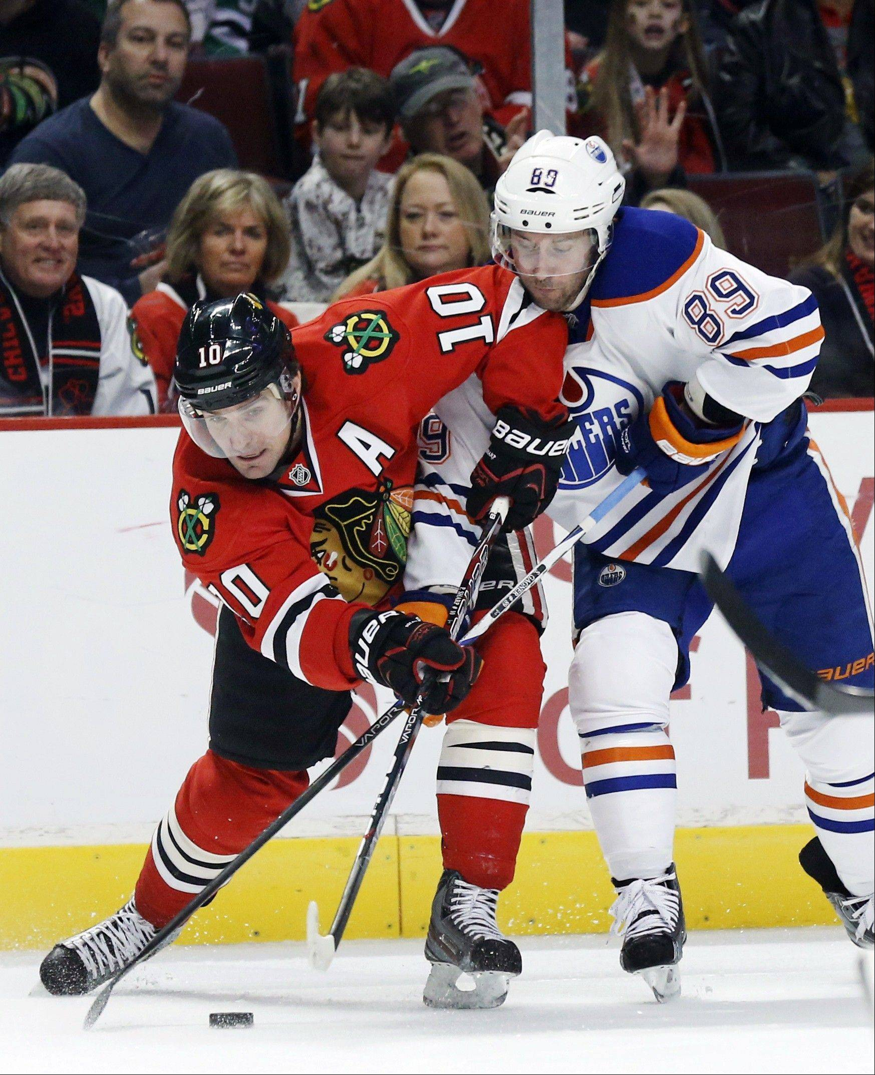Blackhawks sniper Patrick Sharp battles Edmonton Oilers center Sam Gagner for a loose puck during Monday's first period at United Center.