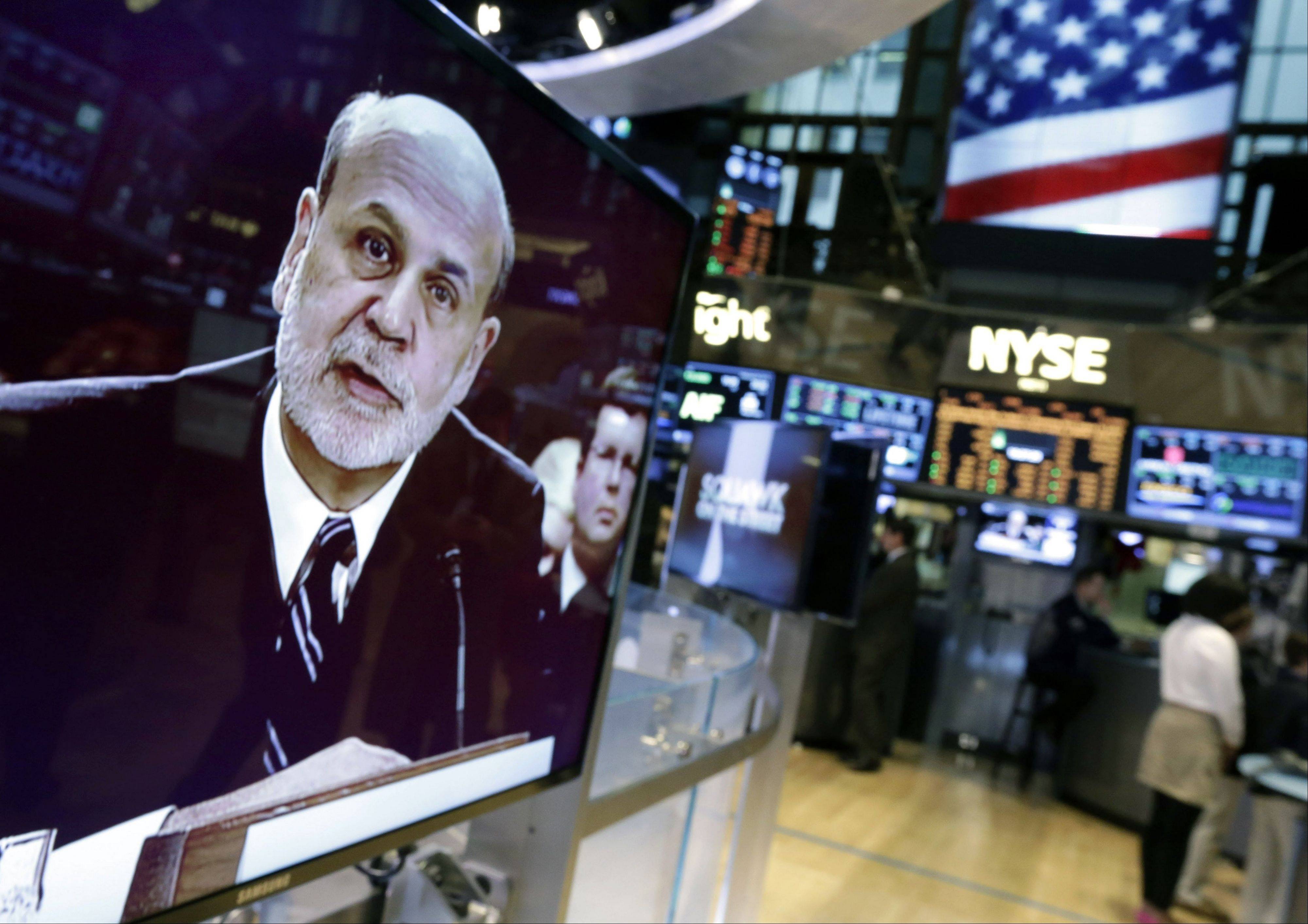 Federal Reserve Chairman Ben Bernanke is seen on a monitor on the floor of the New York Stock Exchange Tuesday. The Federal Reserve�s low interest-rate policies are giving key support to an economy still burdened by high unemployment, Bernanke told Congress.