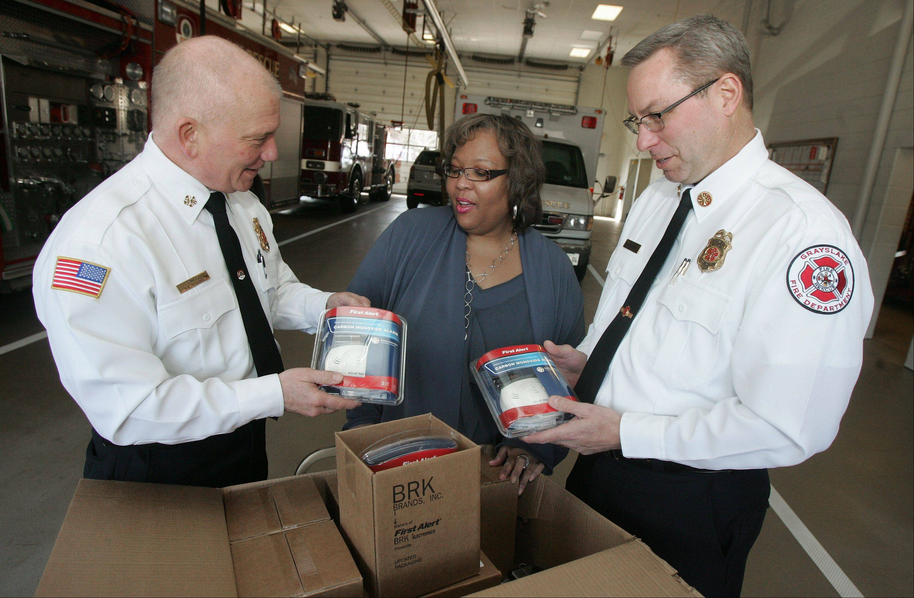 Andrea Danks, a representative for North Shore Gas, delivers boxes of carbon monoxide detectors to Mundelein Fire Chief Tim Saschko, left, and Grayslake Fire Chief John Christian at the Mundelein Fire Department. North Shore Gas donated the First Alert detectors to the two departments to be given to residents in need.