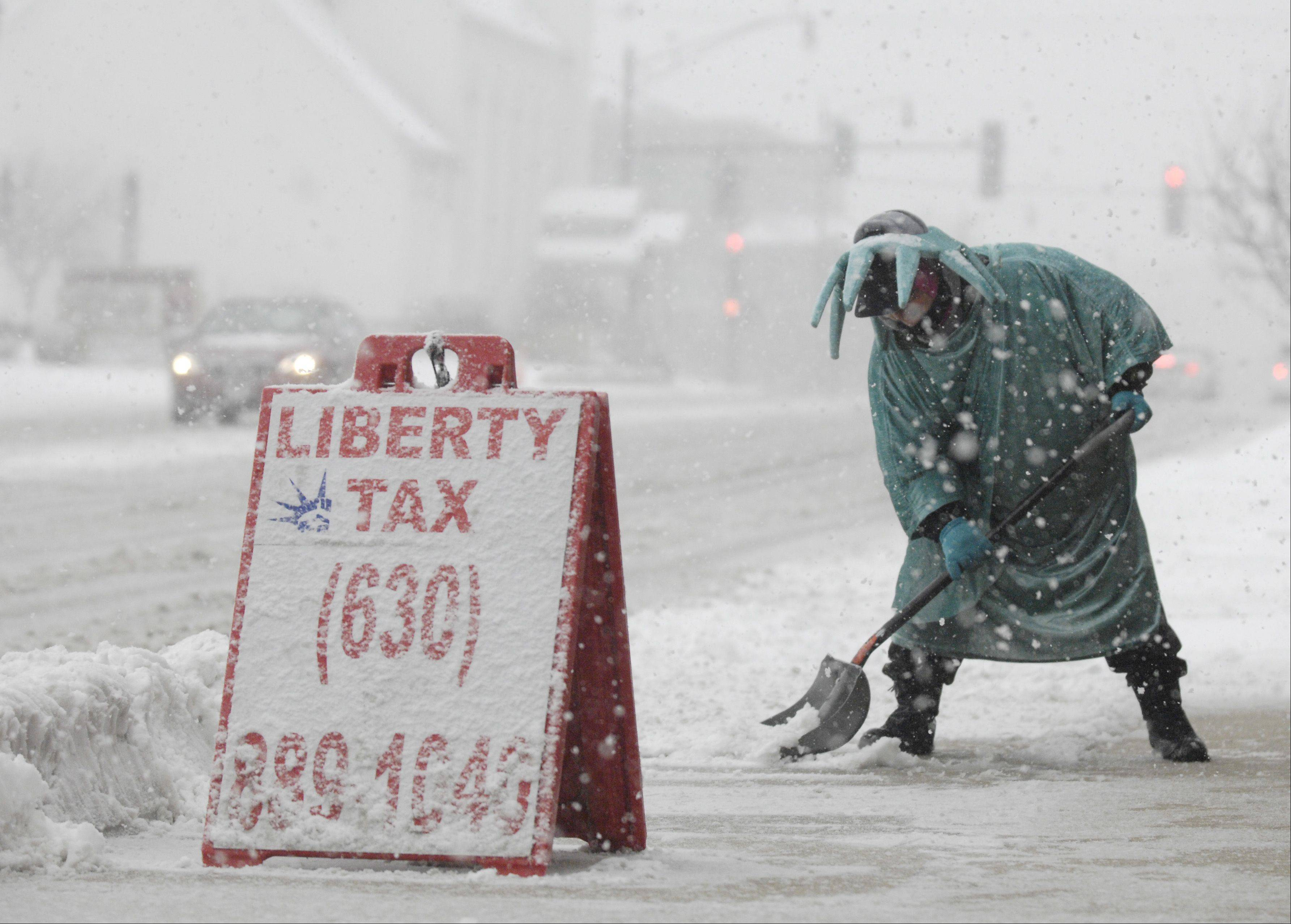 Actor Steve Sparks shovels snow dressed as the Statue of Liberty in front of Liberty Tax in Lombard, Tuesday.