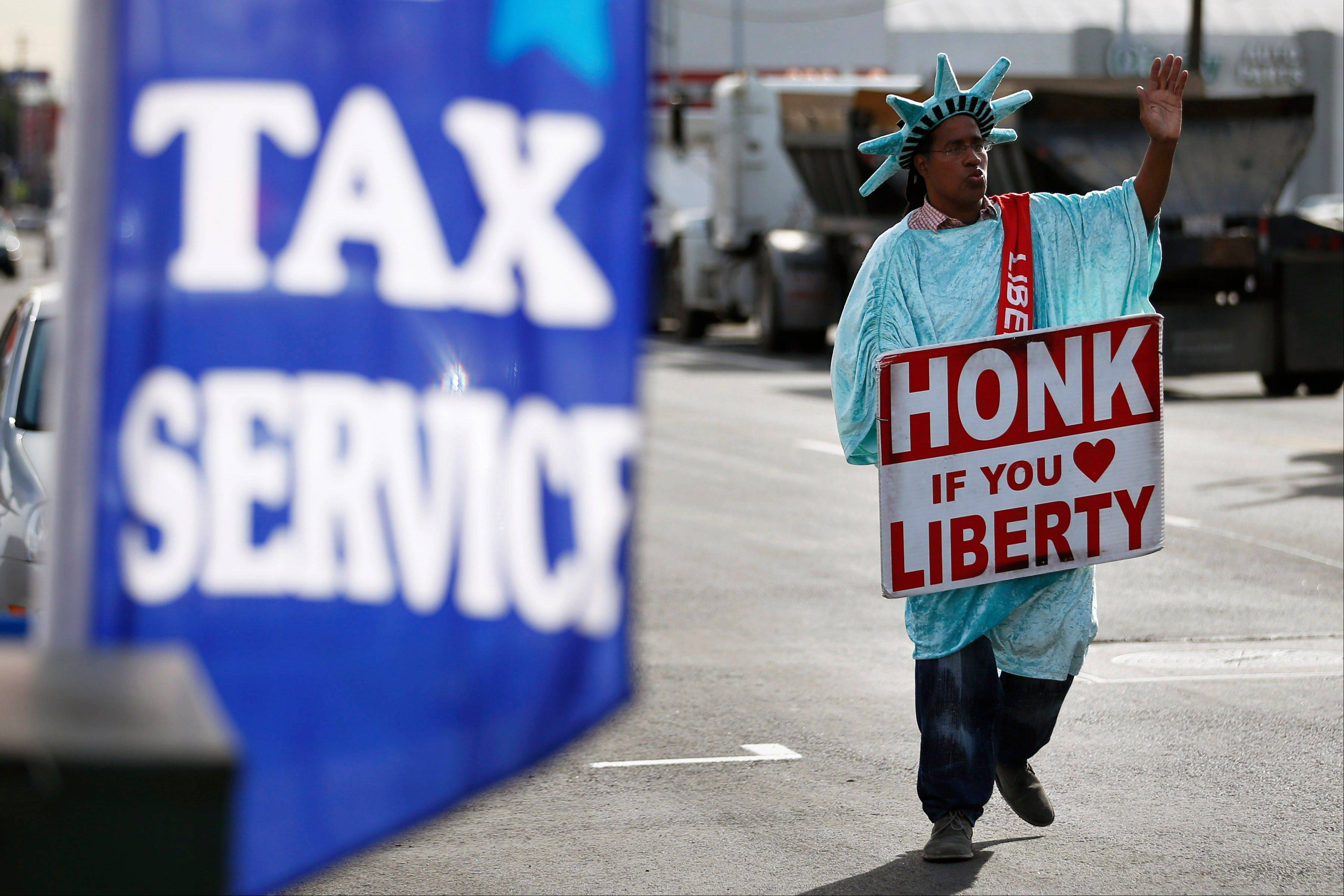 Dressed as the Statue of Liberty, an employee waves to passing motorists while holding a sign to advertise for Liberty Tax Service in Los Angeles. With tax season in full swing, a newly released poll says an overwhelming majority of adults don't believe it is ever OK to cheat on their income taxes, with most citing personal integrity as the biggest reason why.