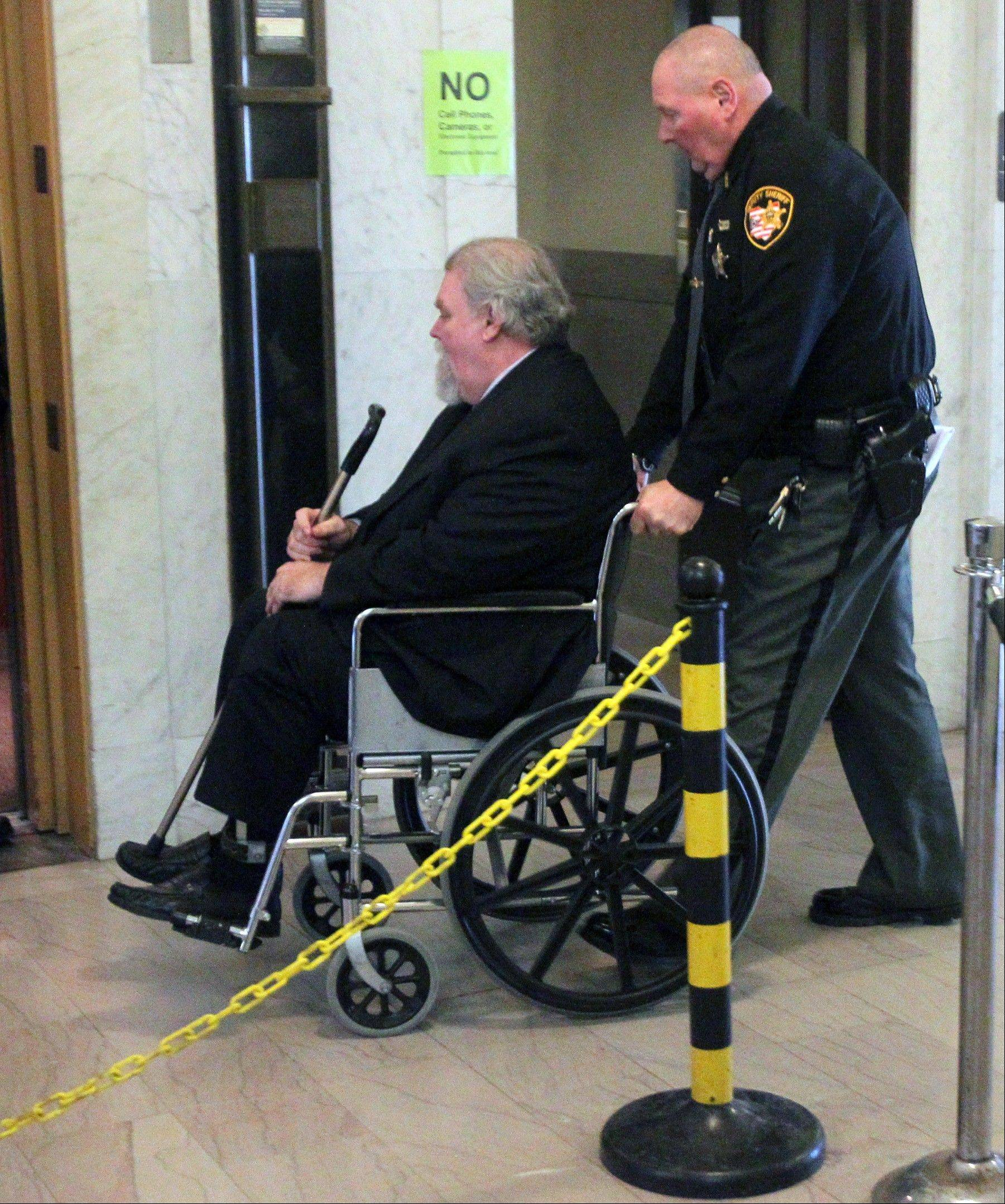 Associated PressA Summit County Sheriff's Deputy wheels defendant Richard Beasley to the elevator at the conclusion of testimony in his murder trial in Summit County Court on Monday.