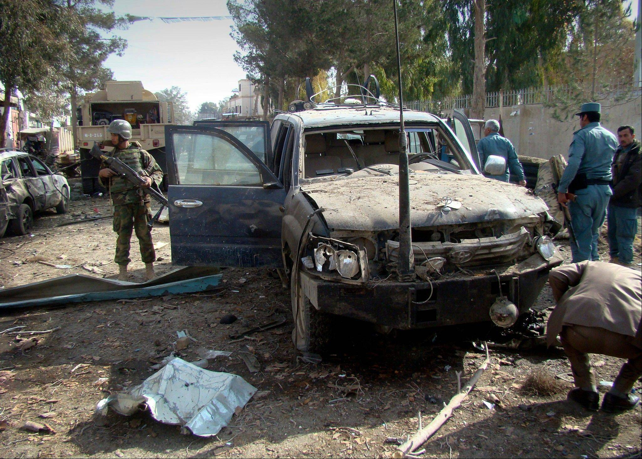 An Afghan solider, left, stands guard at the scene of a suicide attack in Lashkar Gah, Helmand province, in this Jan. 26, 2012, file photo,