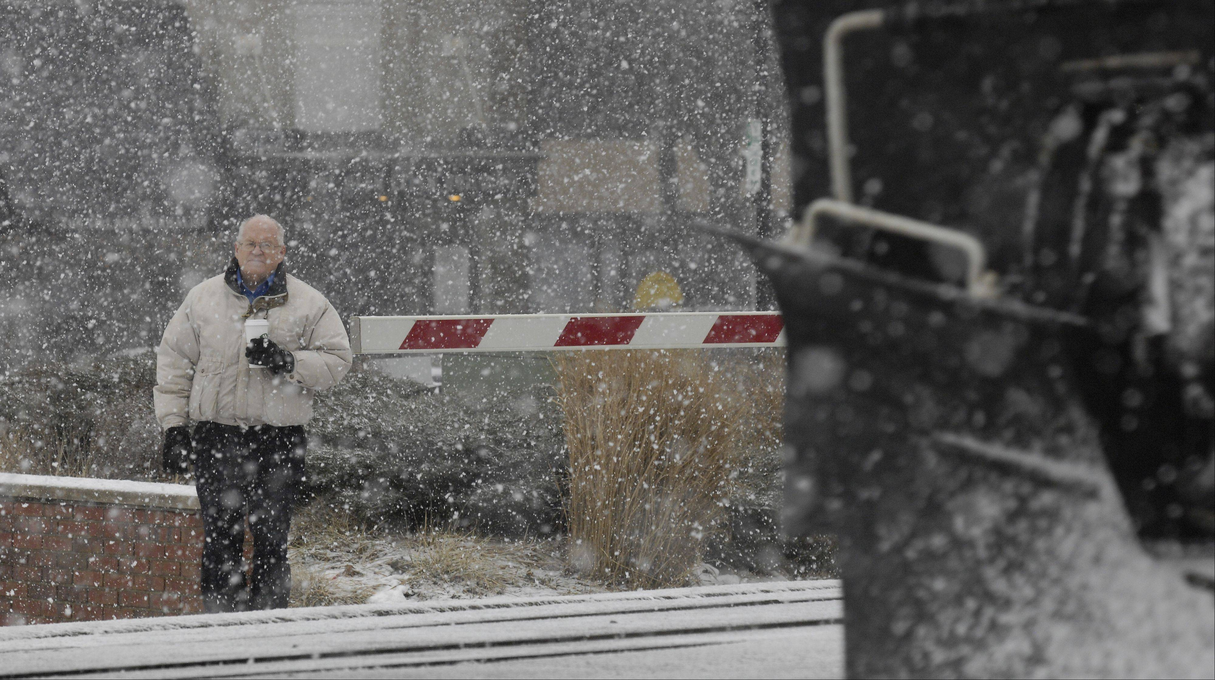 Mark Binkerd of Warrenville waits in the blowing snow and sleet for a train to pass, in Glen Ellyn, Tuesday morning.