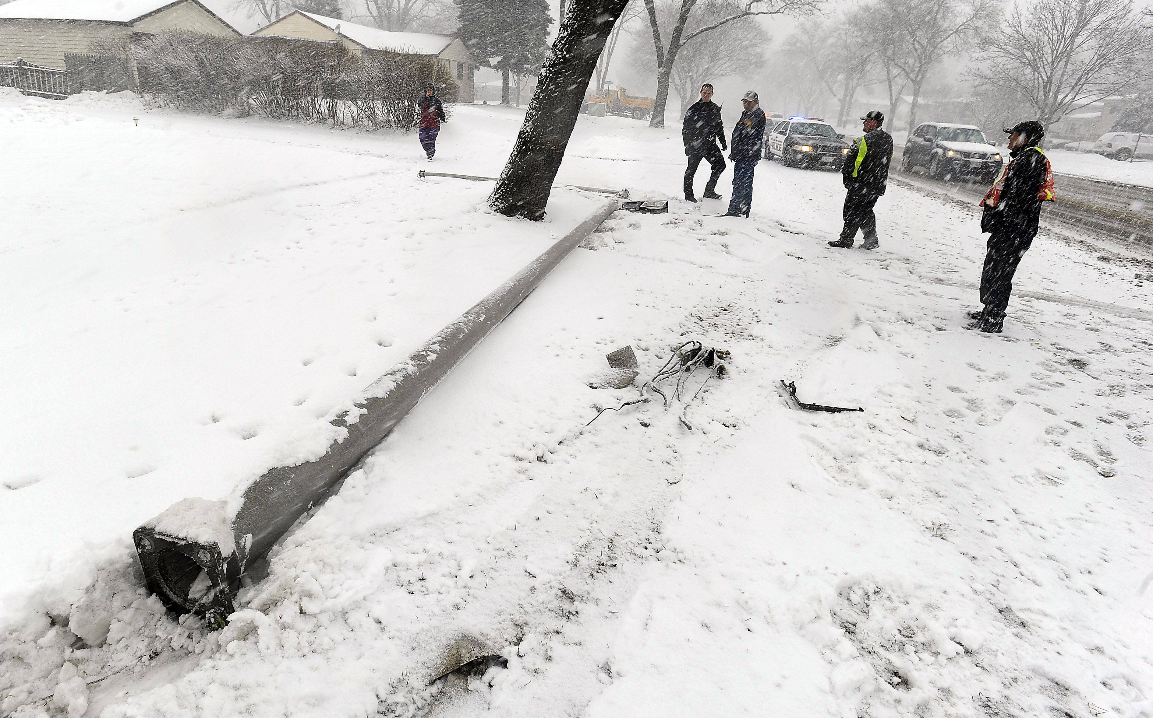 Slick road that drivers endured caused accidents such as this one in Rolling Meadows where a driver plowed over a streetlight as the wet heavy snow moved through the Northwest suburbs area on Tuesday.