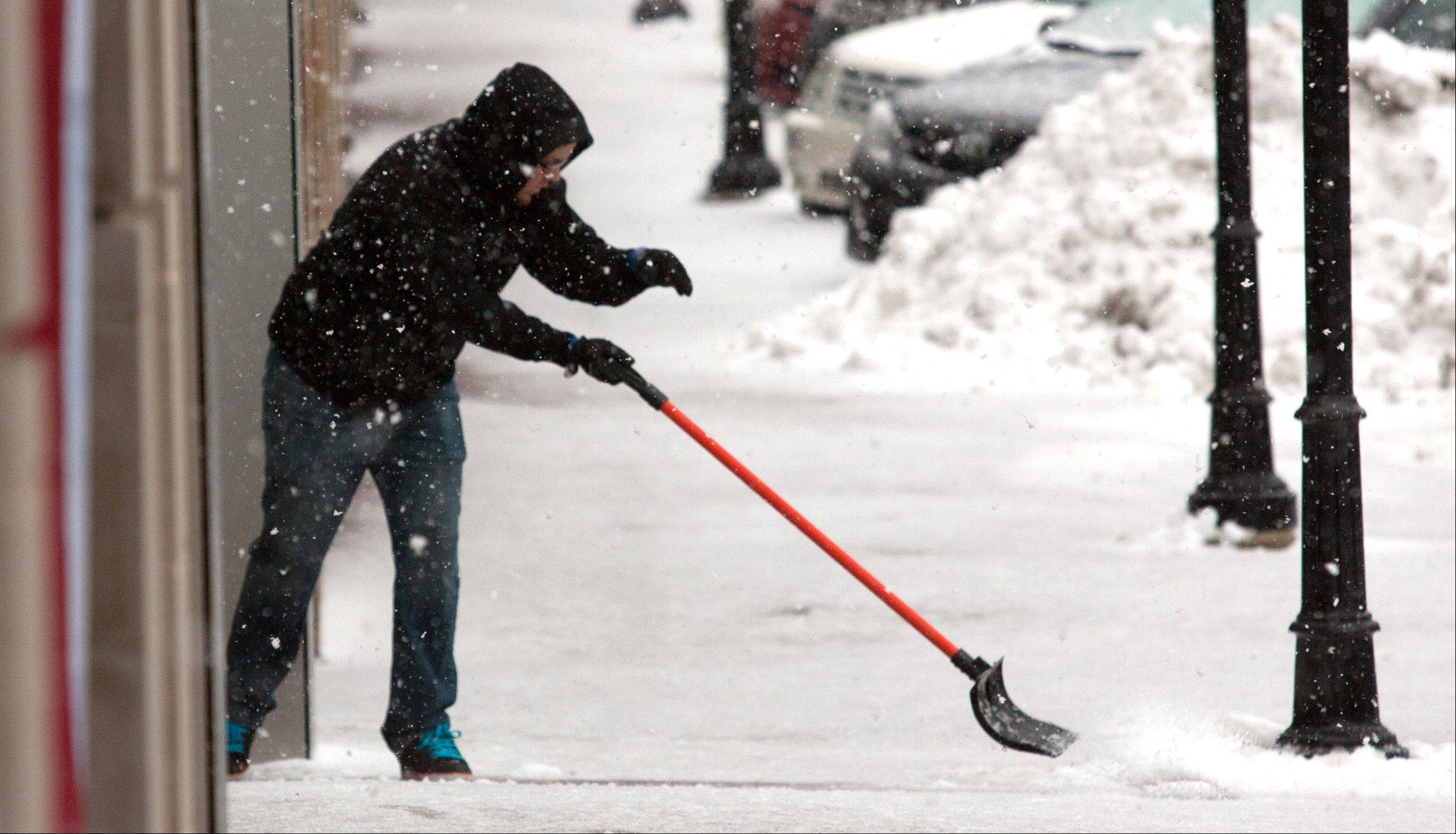 An Apple Store employee clears the sidewalk, as a winter storm passes through downtown Naperville.