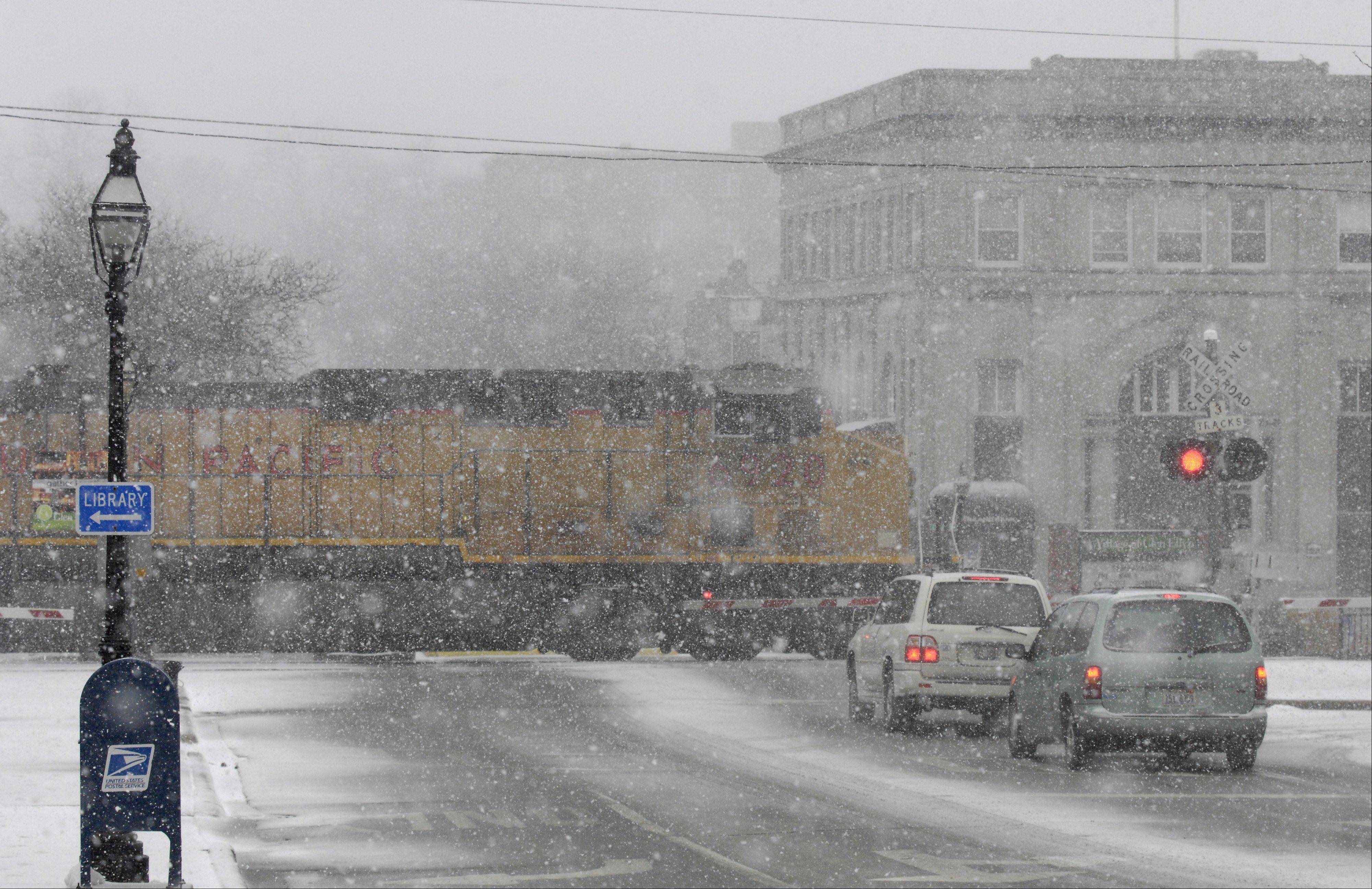 The blowing snow and sleet obscures the view of a passing freight train in downtown Glen Ellyn, Tuesday morning.