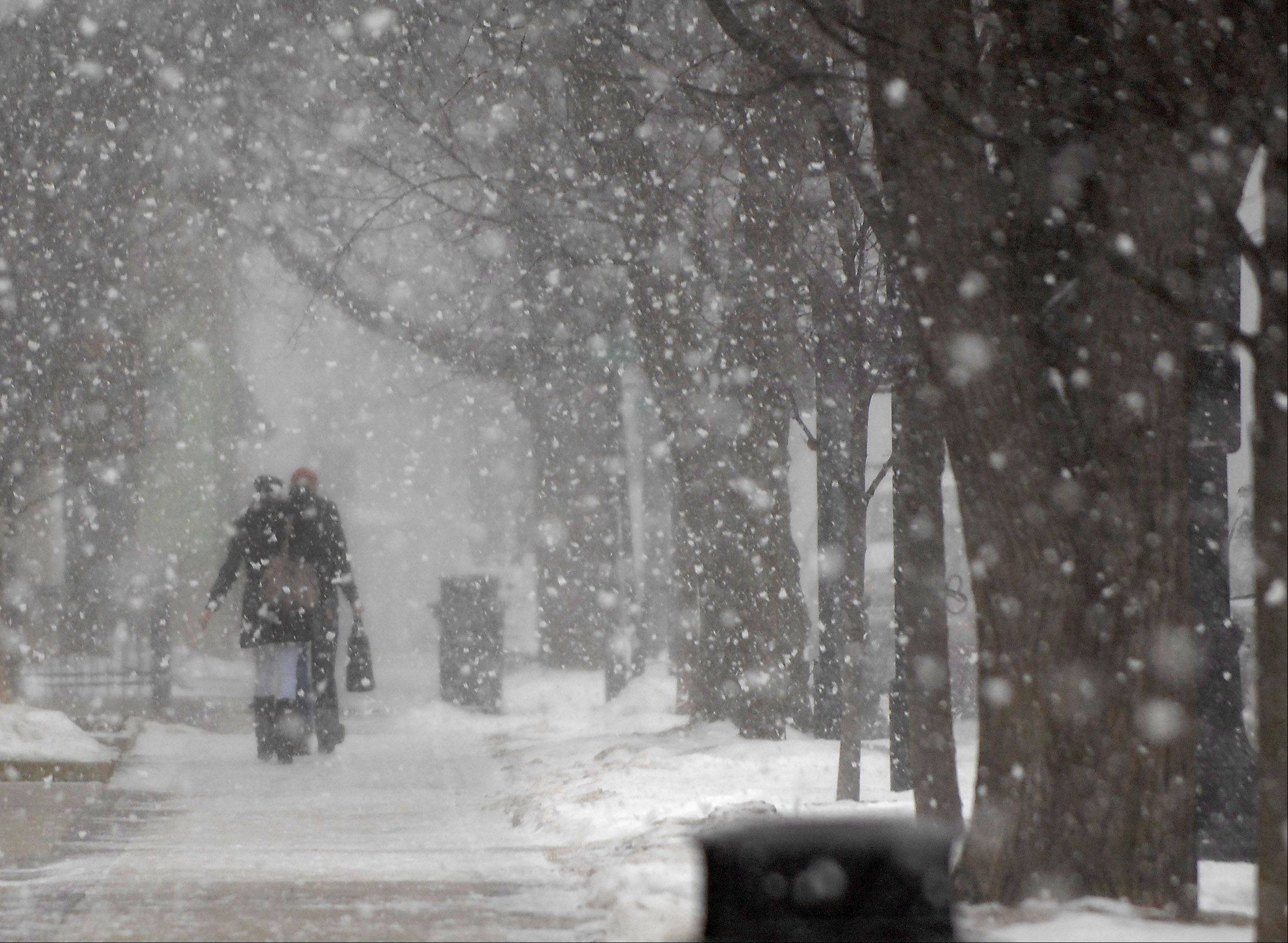 Shoppers make their way along Third Street in Geneva as the snow starts to fall Tuesday morning.