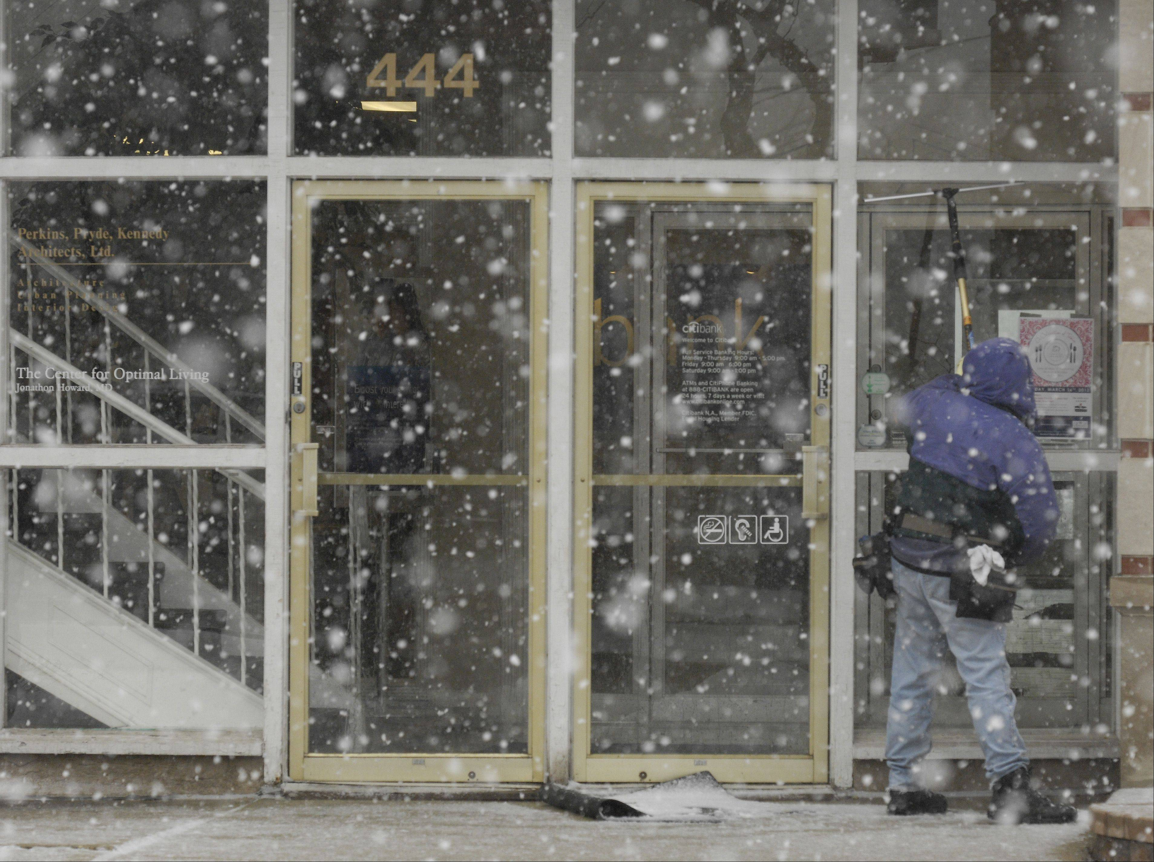 Tim O'Malley of Elk Grove washes the windows the Citibank building in Glen Ellyn as the blowing snow and sleet start up Tuesday morning.