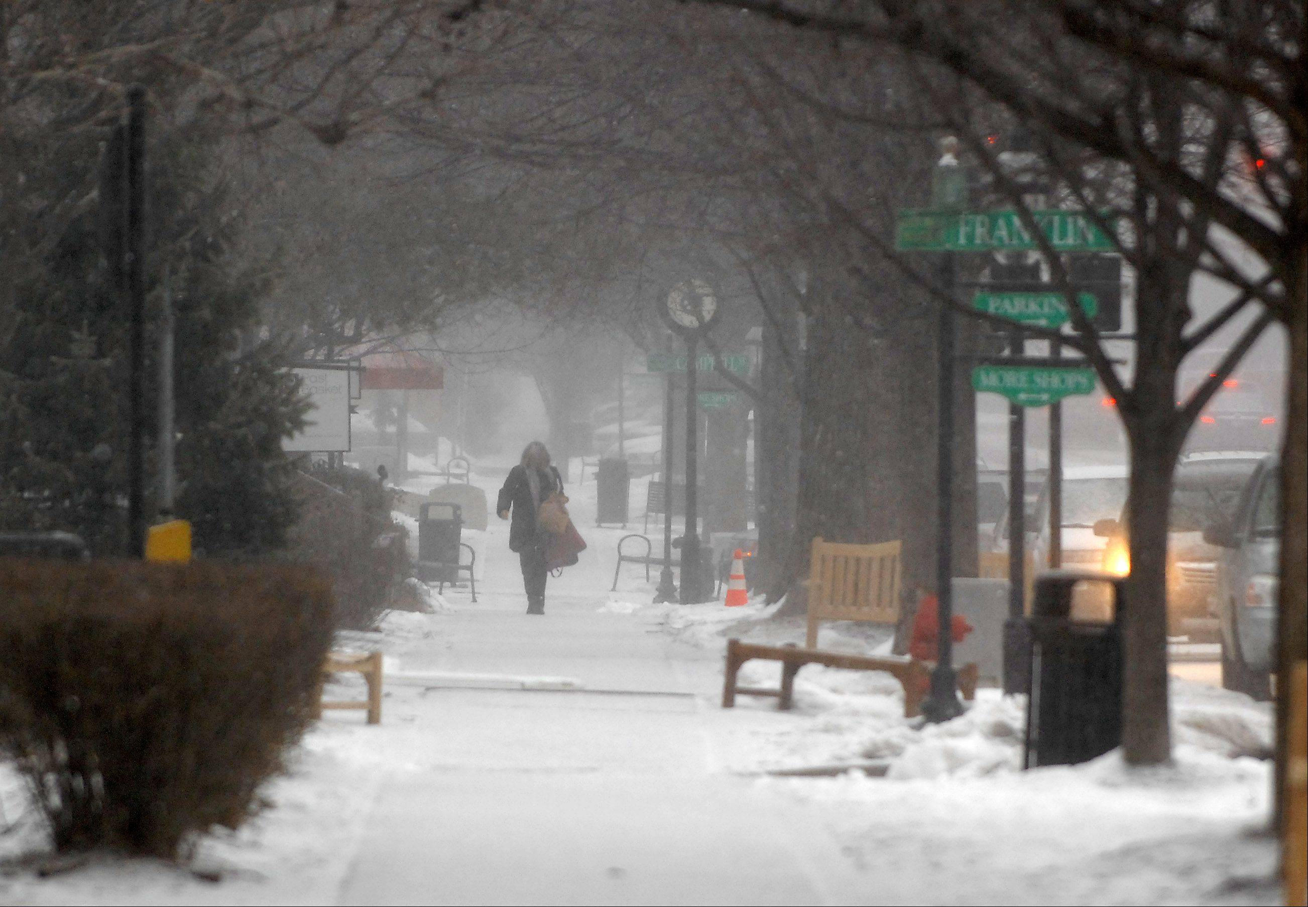 A shopper makes her way along Third Street in Geneva as the snow starts to fall Tuesday morning.