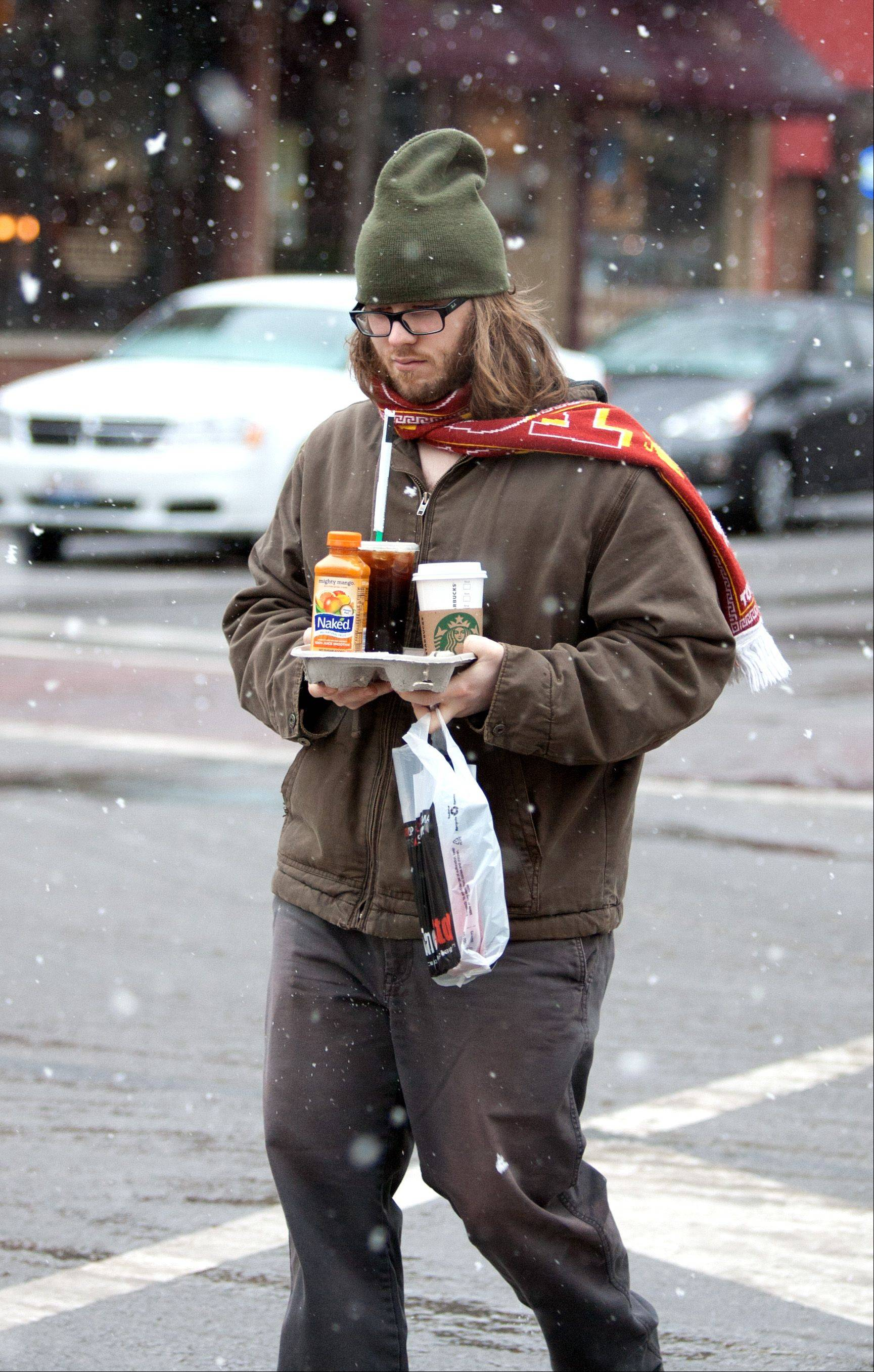 "Jason Nawara crosses Main and Jefferson Streets, as a winter storm passes through downtown Naperville. ""After living for thirty years in this weather, I'm moving to California in eight hours,"" he said."