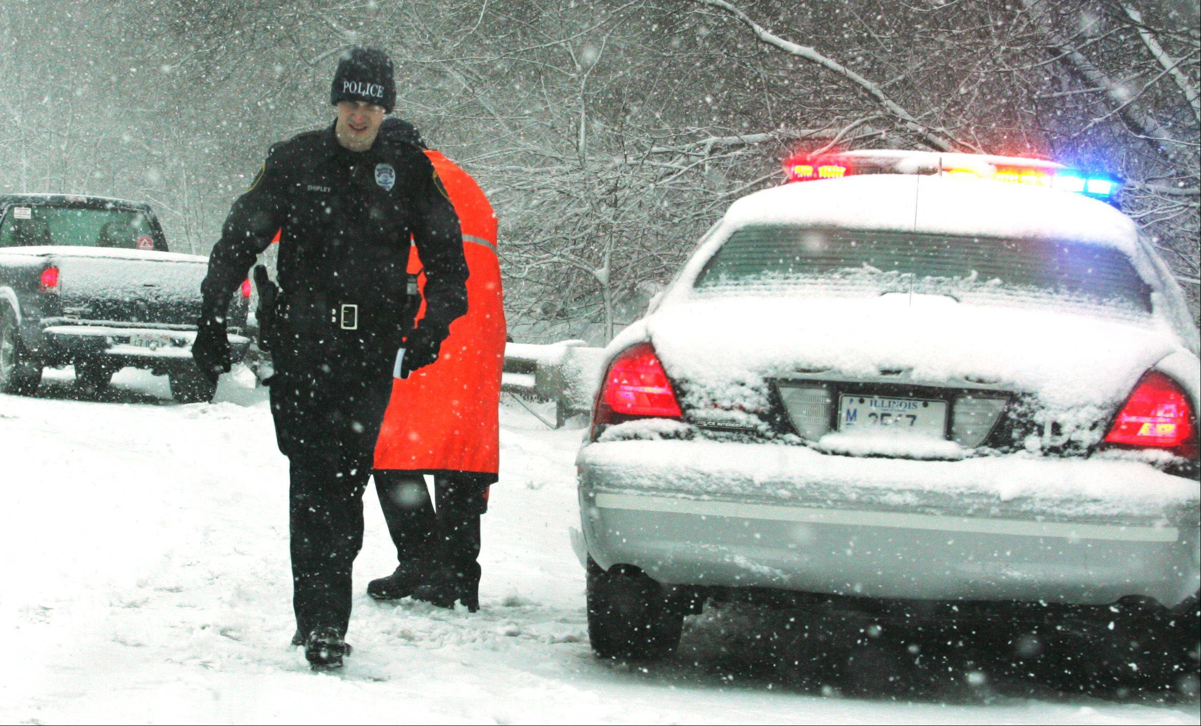 A West Dundee police officer battles the elements at the scene of a multicar crash which sent at least one person to the hospital and snarled traffic on Route 31 near Boncosky Road in West Dundee Tuesday afternoon.