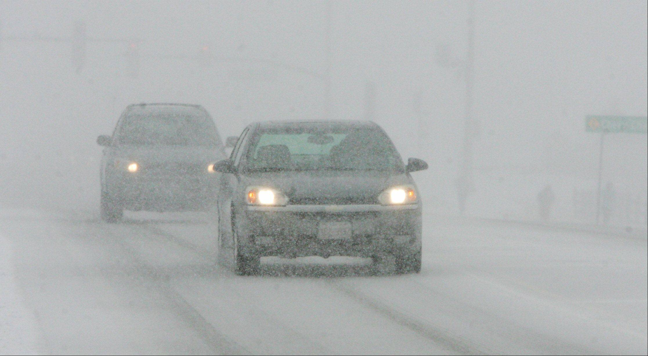 Cars try to navigate along Hawley Street in Mundelein during the snowstorm that hit Lake County on Tuesday. The blizzard was expected to drop up to six inches of snow in the area.