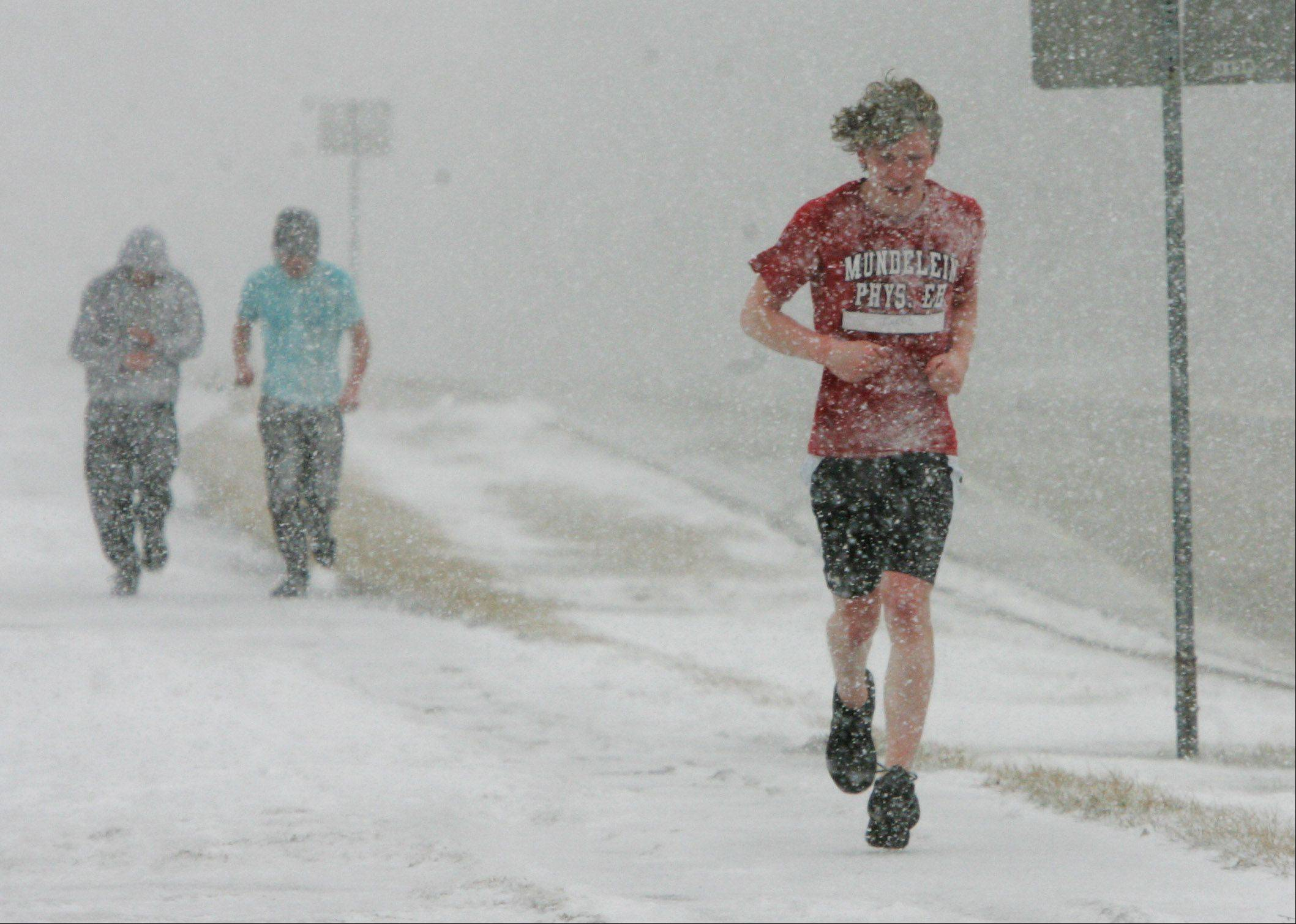 Junior Jacob Petri runs with other Mundelein High School students in a strength and conditioning class during the snowstorm that hit Lake County on Tuesday. The blizzard was expected to drop up to six inches of snow in the area.