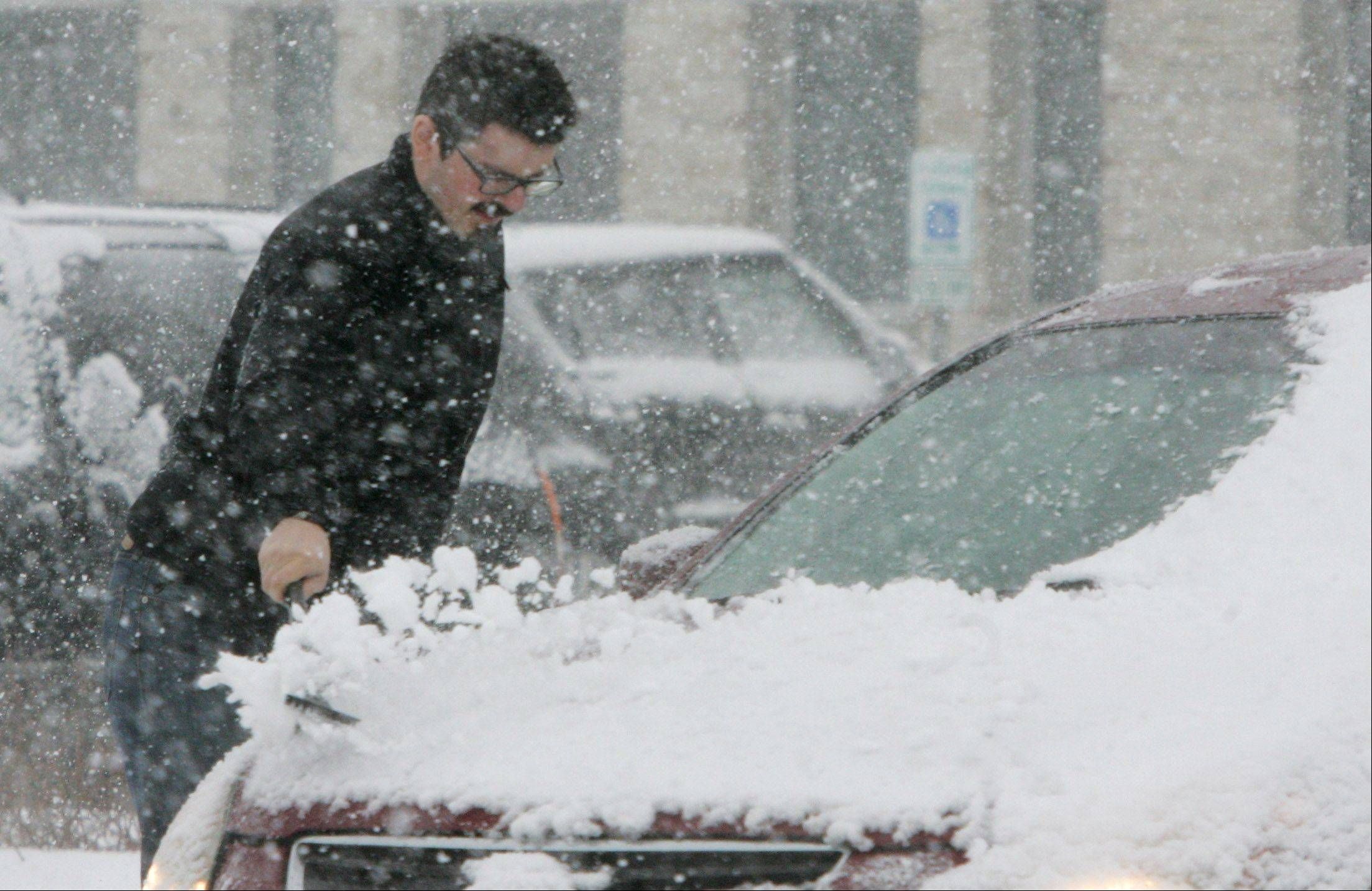 Alex Vazic, of Libertyville, clears the snow from his car in Vernon Hills during the snowstorm that hit Lake County on Tuesday. The blizzard was expected to drop up to six inches of snow in the area.