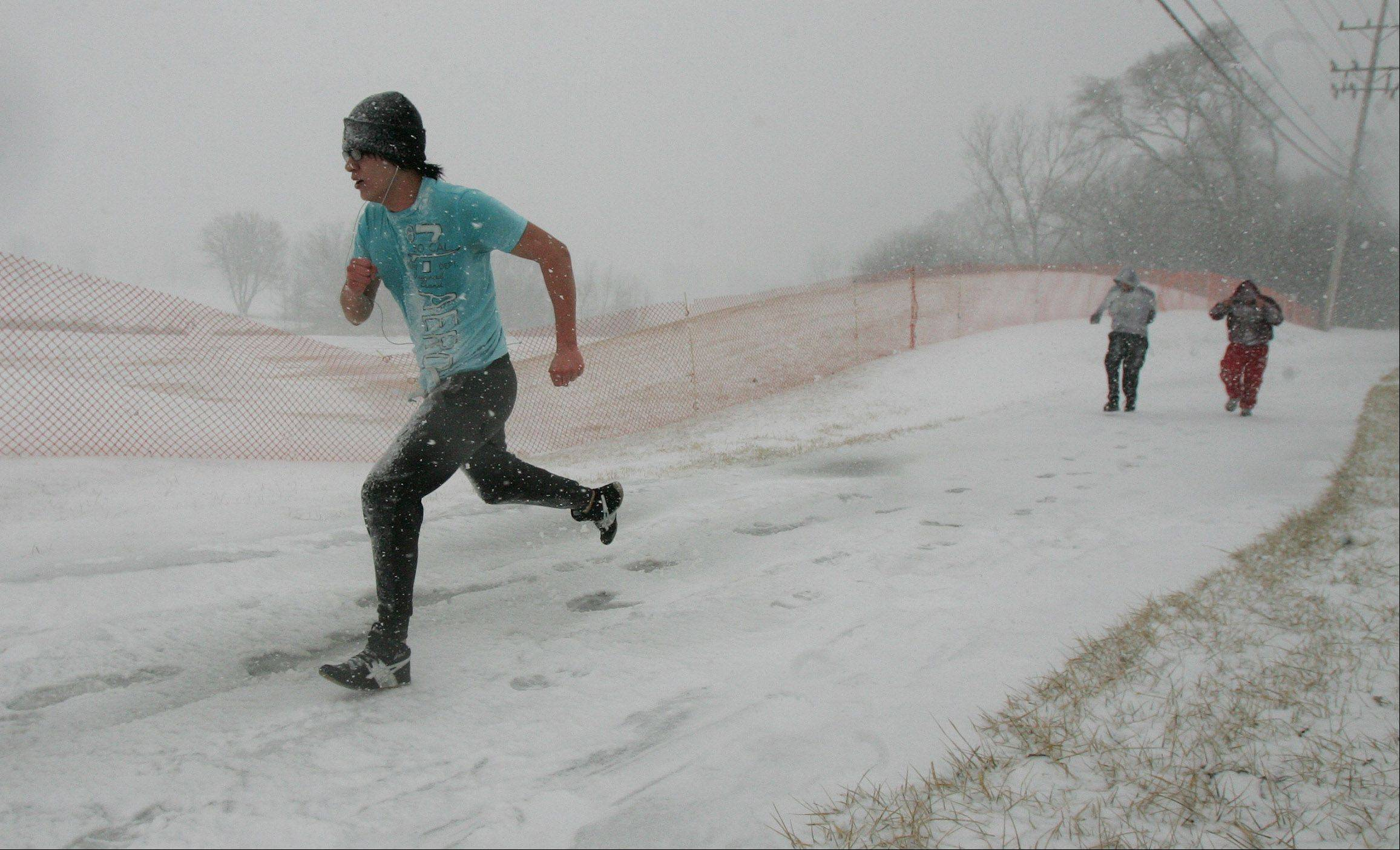 Senior Ricardo Abrego runs with other Mundelein High School students in a strength and conditioning class during the snowstorm that hit Lake County on Tuesday. The blizzard was expected to drop up to six inches of snow in the area.