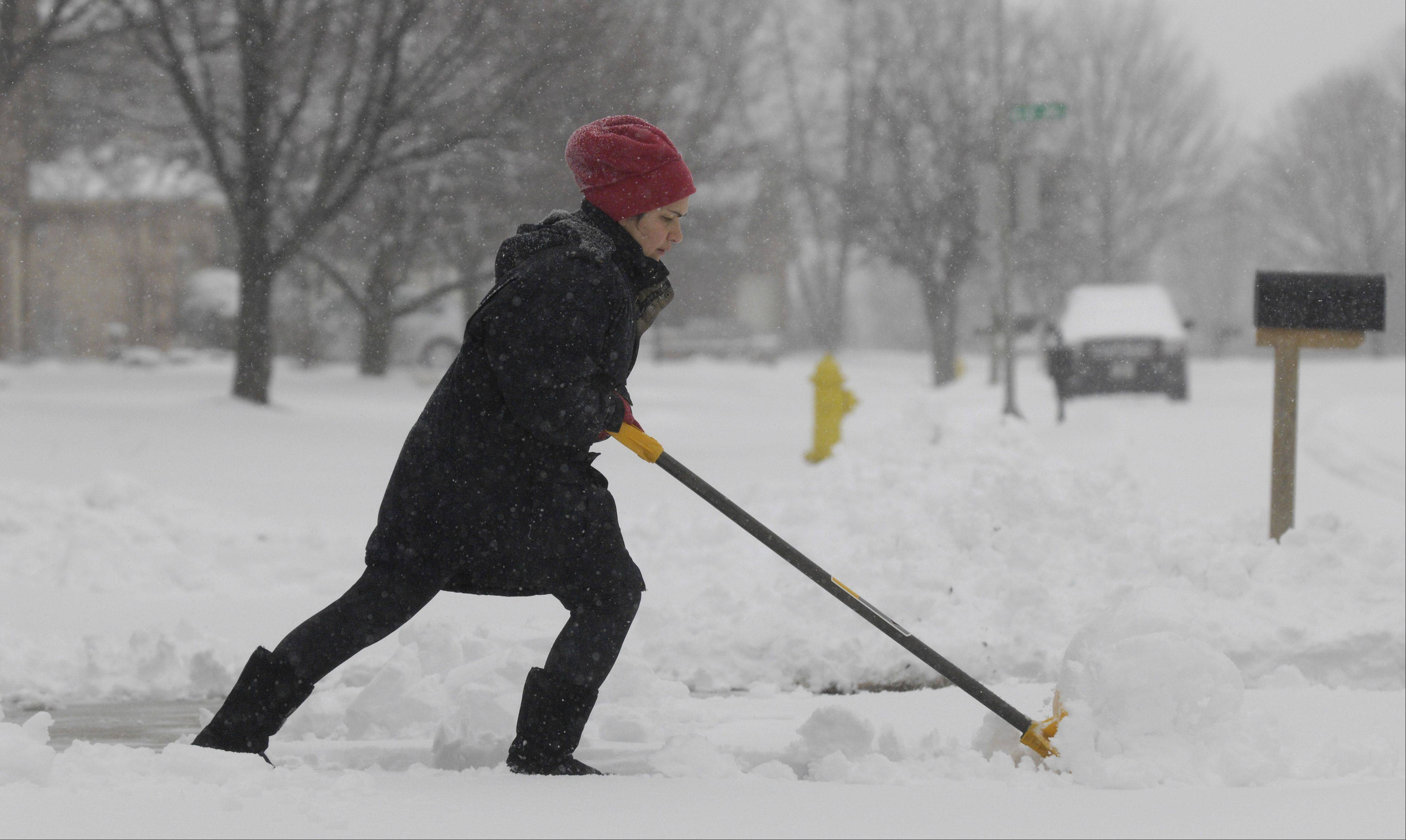 Lynn Fox shovels the snow off her Wheaton driveway, Tuesday. Fox said that shoveling the heavy snow is replacing her daily workout since she wasn't able to get to the gym today.