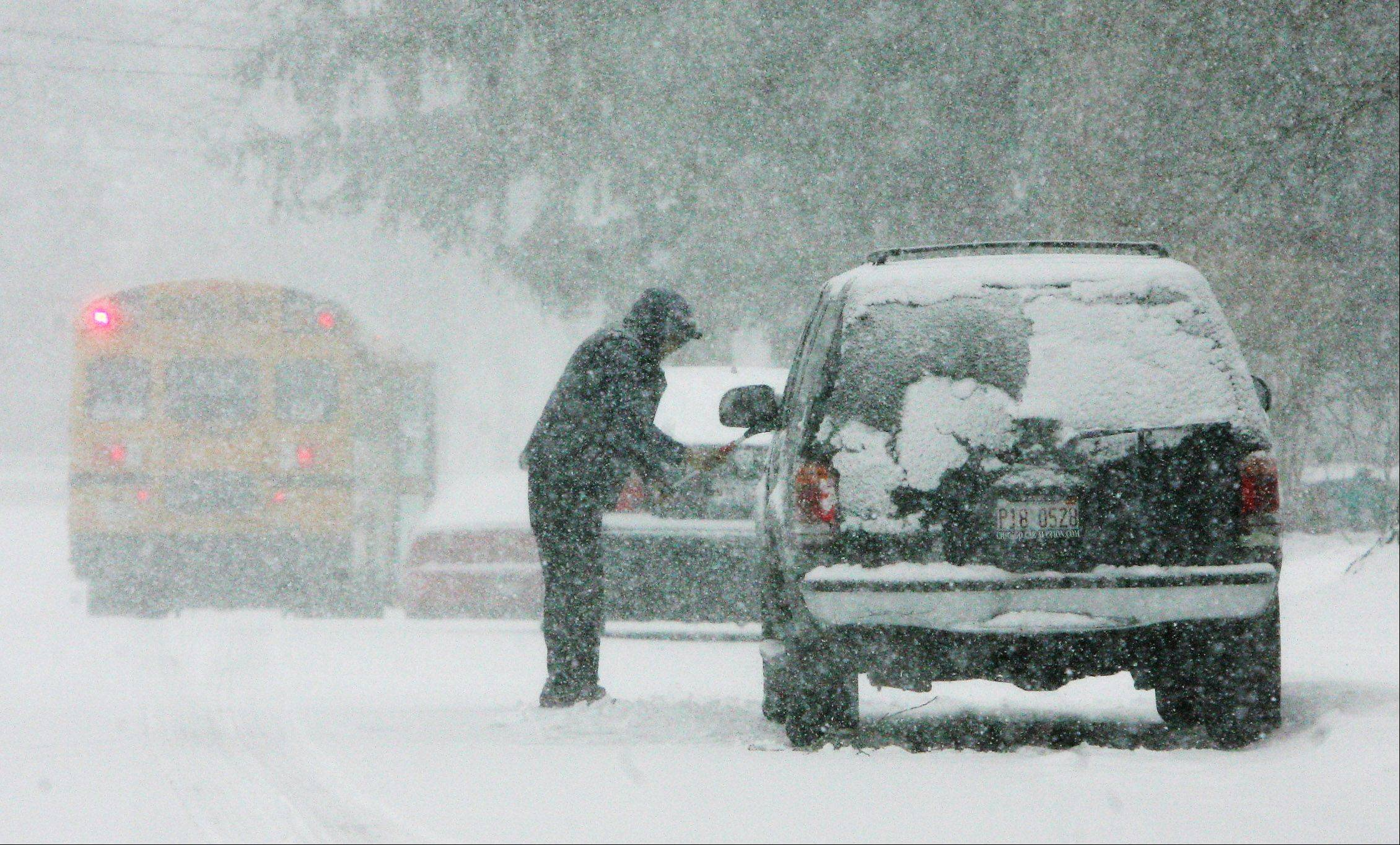 Juan Chavez, of Mundelein, clears the snow from his car during the snowstorm that hit Lake County on Tuesday. The blizzard was expected to drop up to six inches of snow in the area.