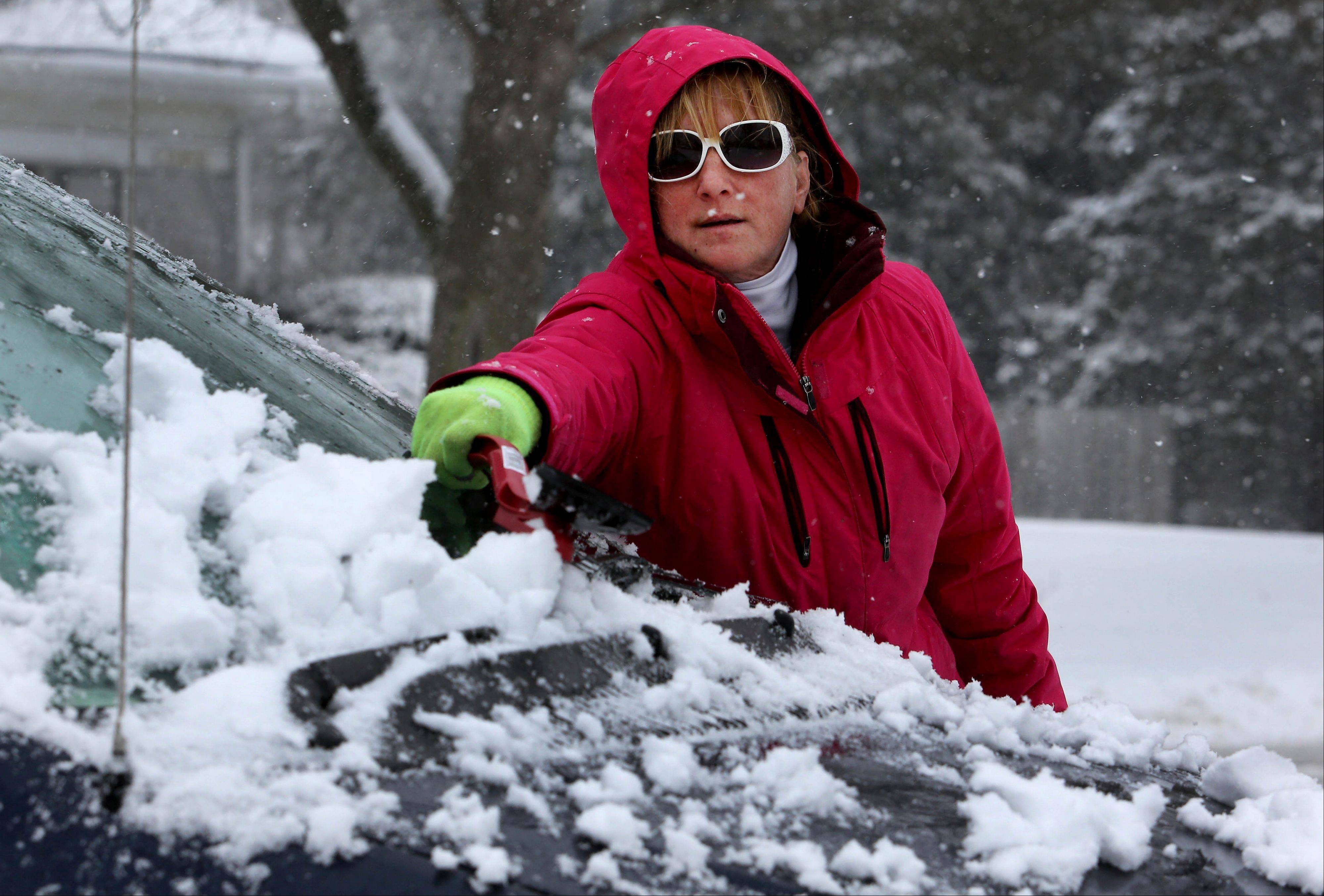 Michelle Miller of Warrenville gets her car cleaned off during the snowstorm on Tuesday.