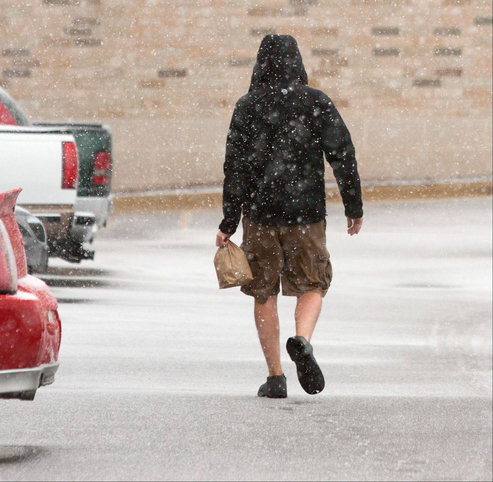 A young man heads to lunch as a winter storm passes through downtown Naperville.