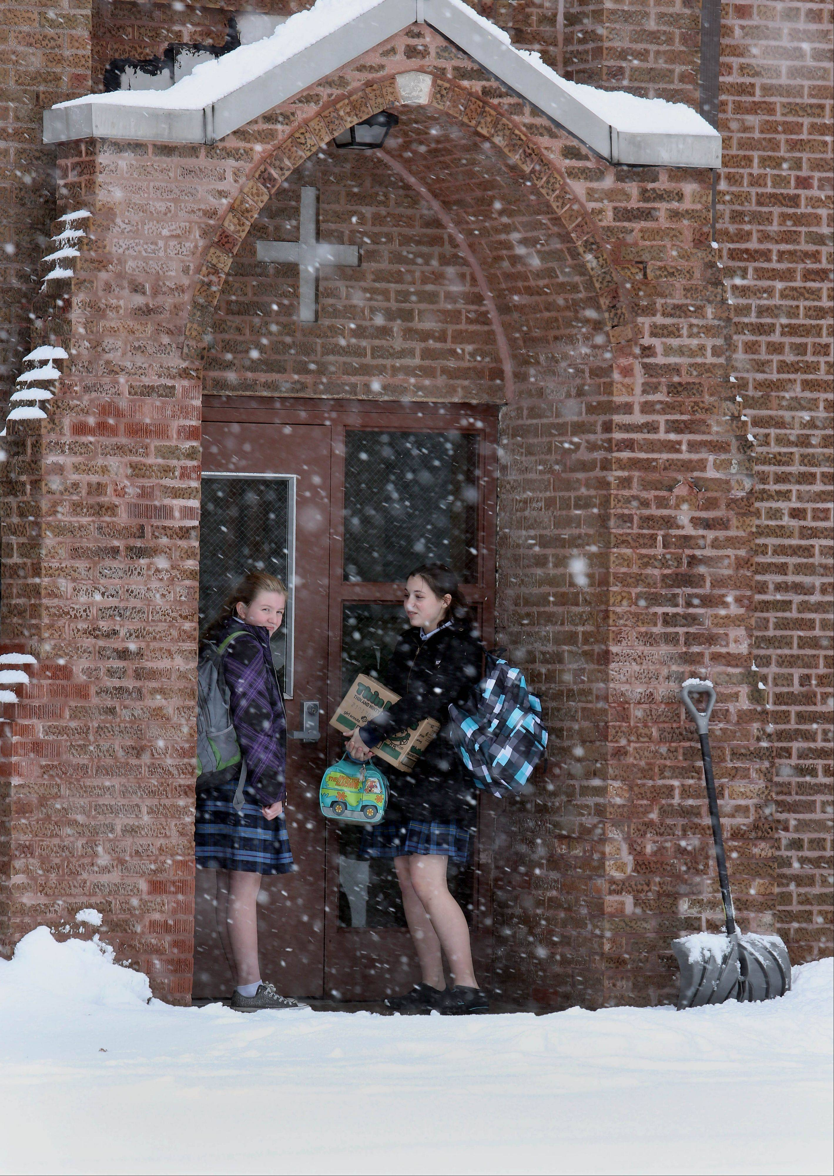 Arielle Duerr, 14, left and Rachael Isdale, 14, right, take shelter in a doorway from the falling snow while waiting for a ride after getting out of St. Irene Catholic School on Tuesday in Warrenville.