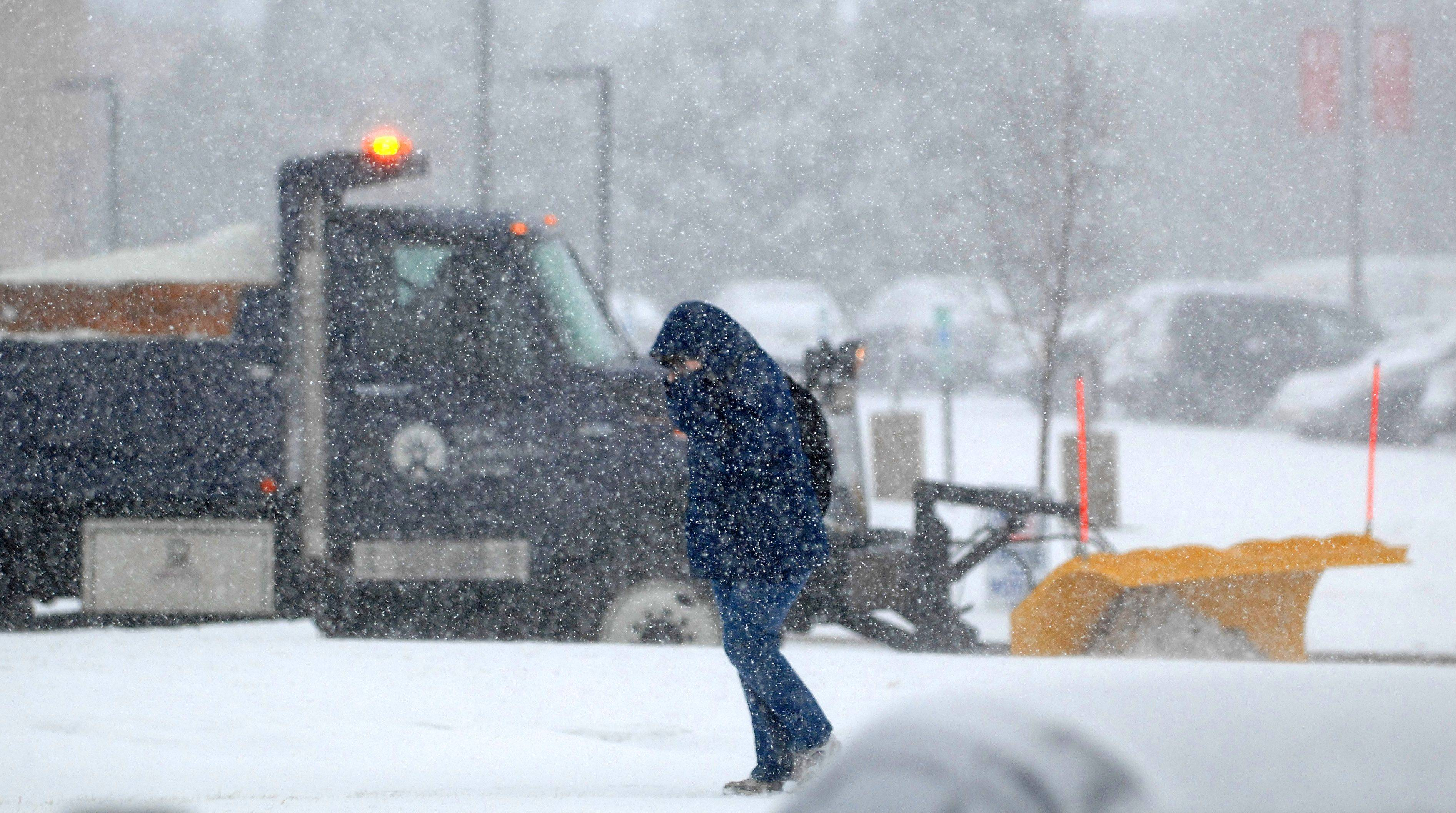 Student Kat Rende of Elgin trudges to her car as the plows get to work at Elgin Community College Tuesday.