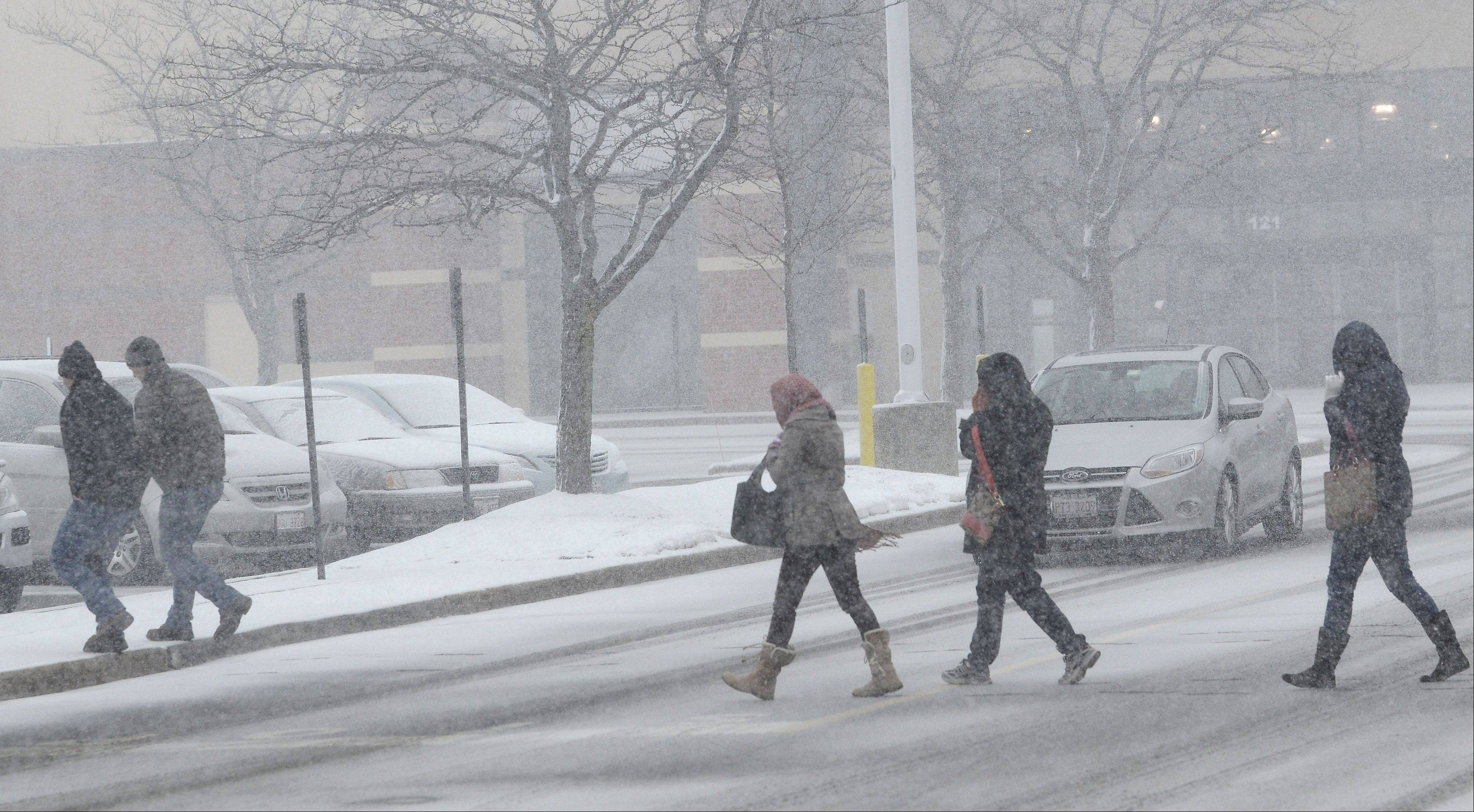 People brave the blizzard-like conditions in Vernon Hills as the latest snowstorm hits Tuesday afternoon.