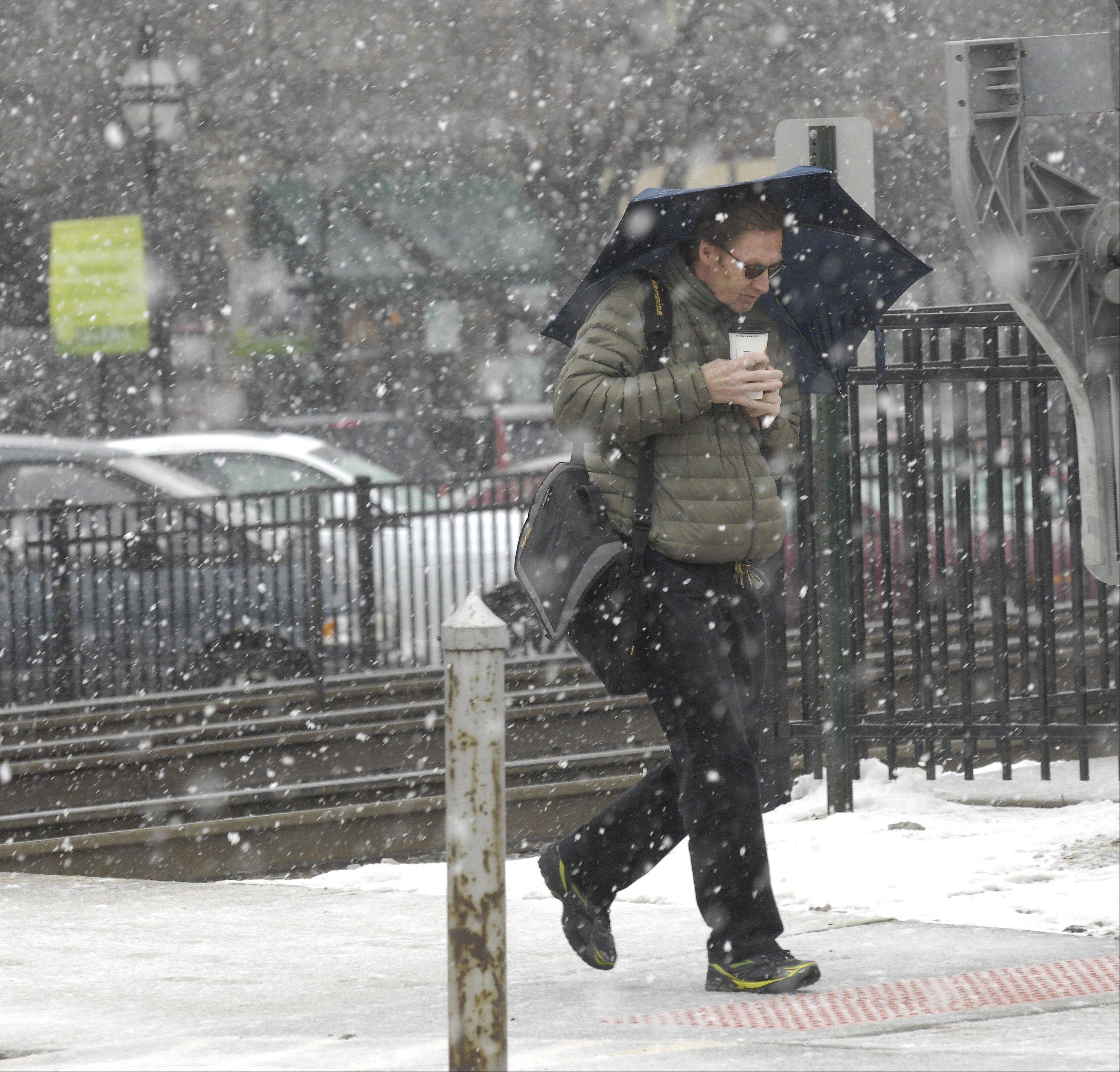 A pedestrian uses an umbrella to block some of the blowing snow and sleet in Glen Ellyn, Tuesday morning.