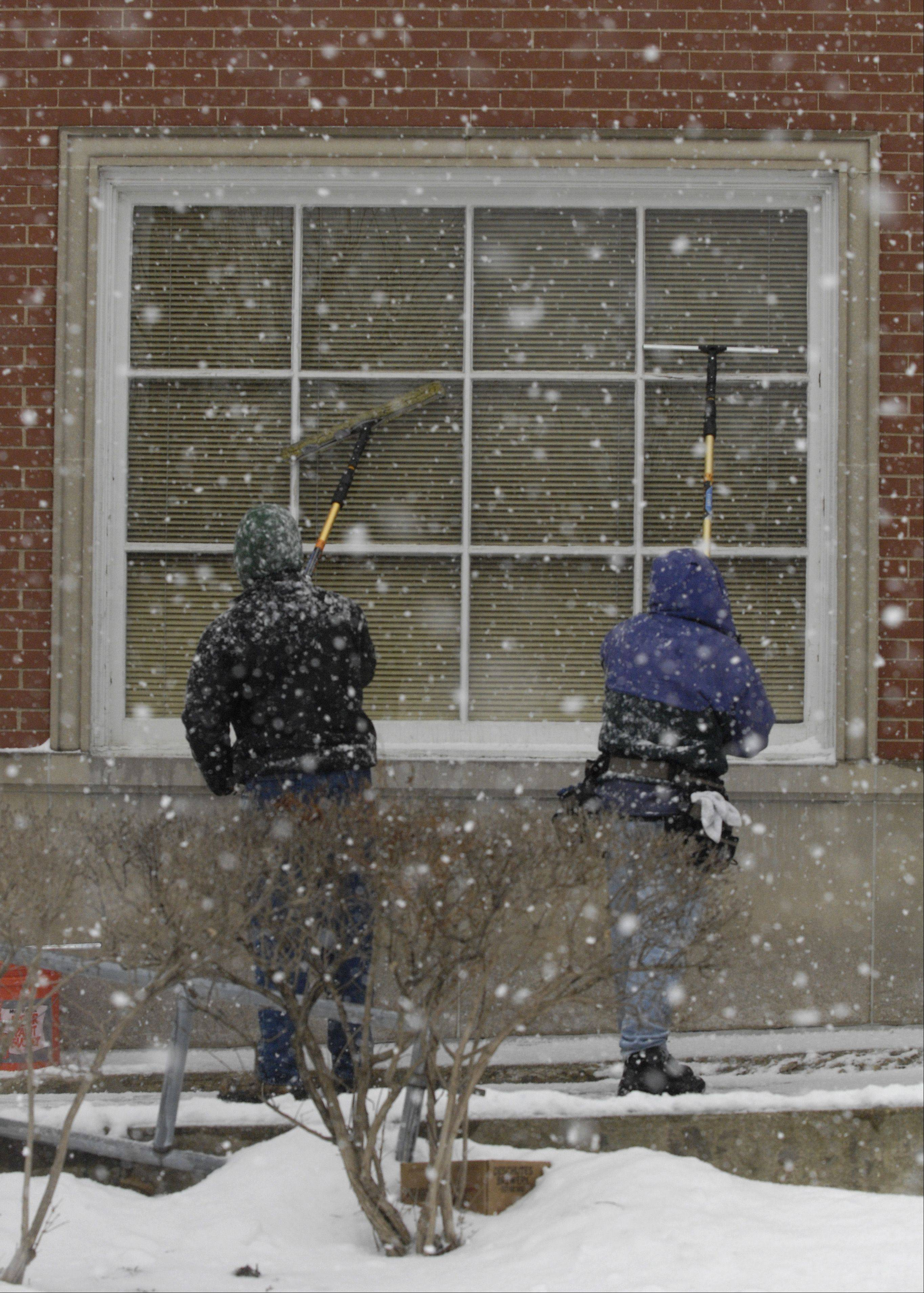 Luke Ellefson and Tim O'Malley of Elk Grove wash the windows the Citibank building in Glen Ellyn as the blowing snow and sleet start up Tuesday morning.