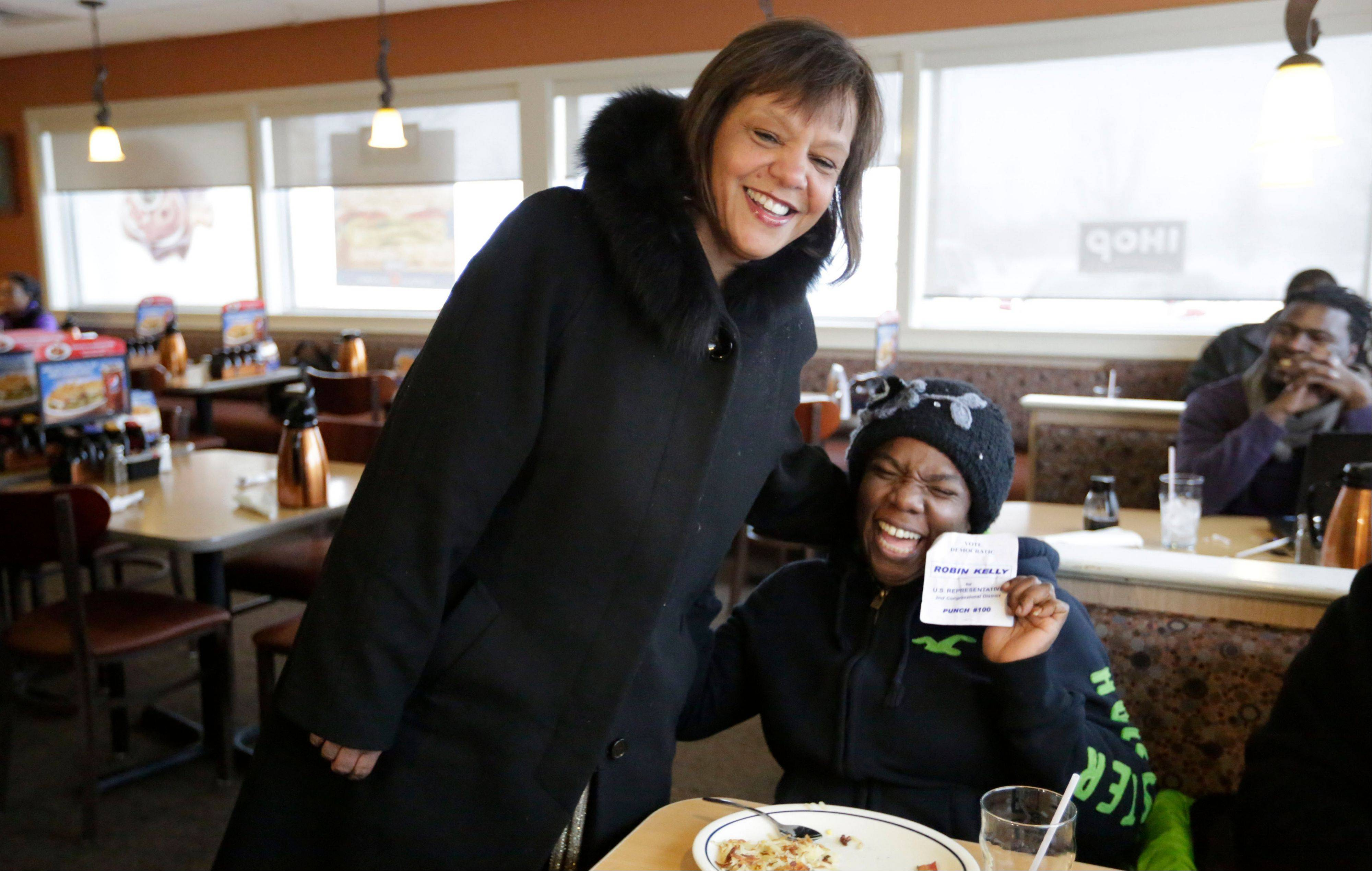 Former state Rep. Robin Kelly finds a supporter in Yolanda Stratton as she campaigns Tuesday at an IHOP in Matteson.