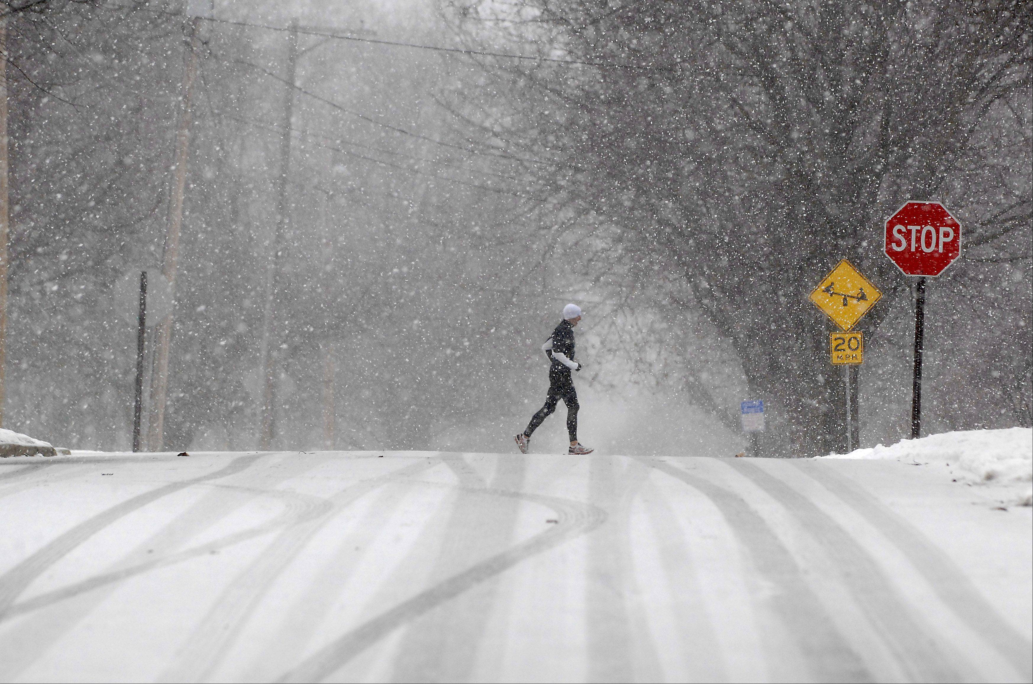 A jogger treks through the snow as it starts to fall in earnest in Geneva Tuesday morning.