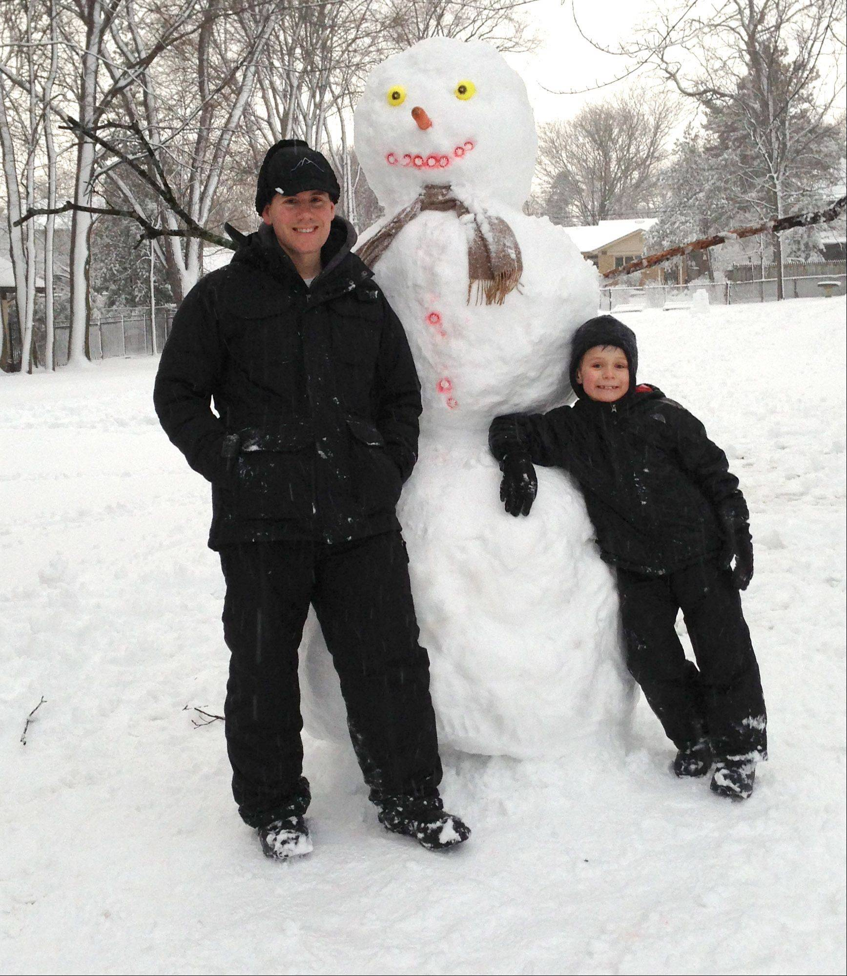 Alex, 8, and father Bill Koc of Batavia built a 7-foot-tall snowman with the snow that fell all day Tuesday.