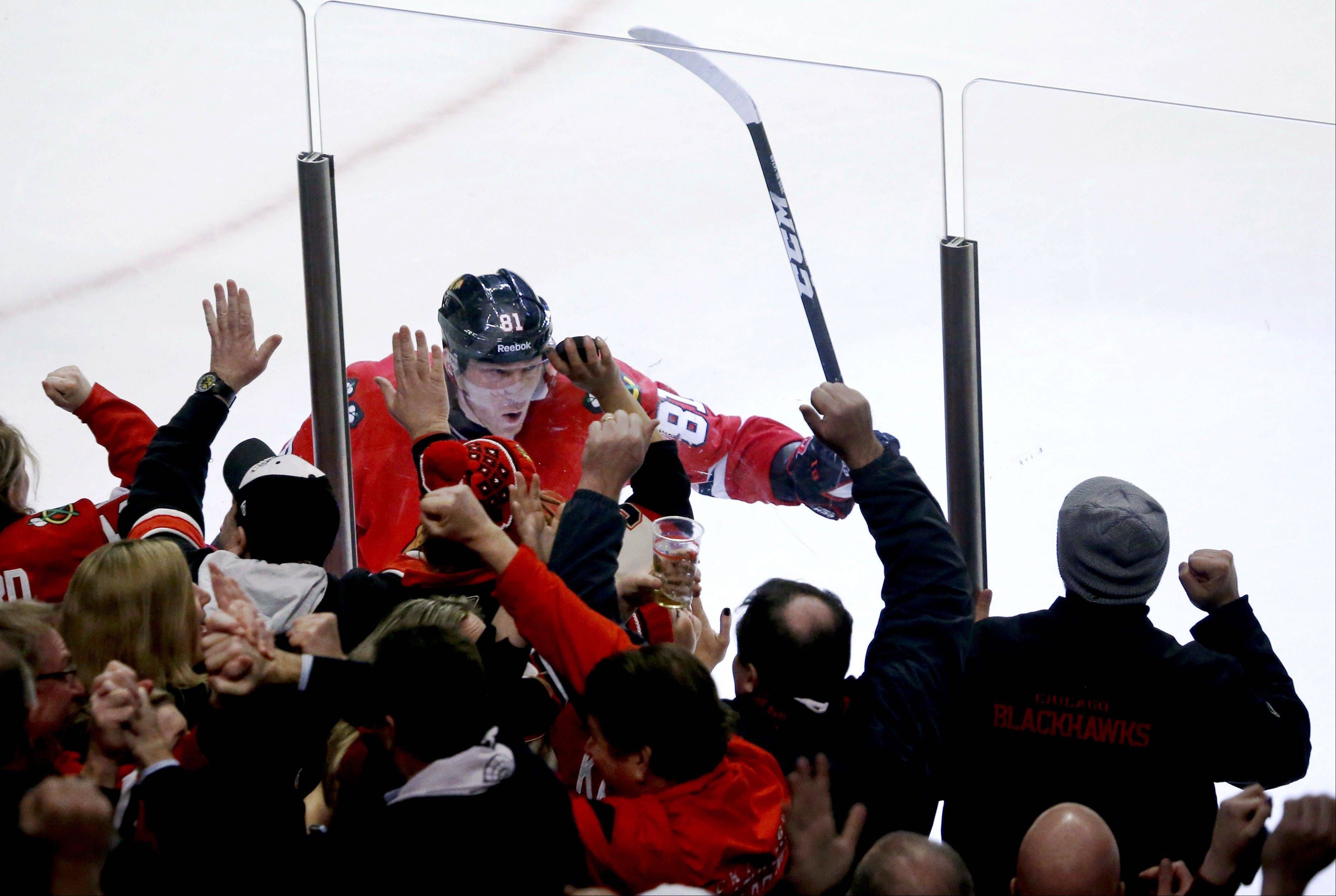 Chicago Blackhawks right wing Marian Hossa celebrates along the boards with fans after scoring the winning goal.